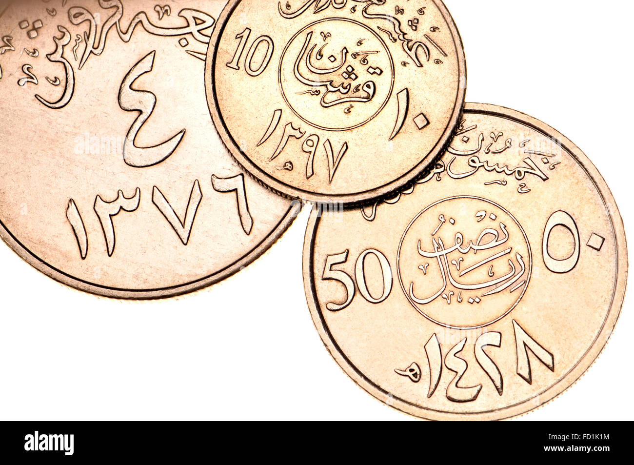 Coins of Saudi Arabia showing Arabic writing and symbols in Eastern Arabic script and dates in the Islamic calendar - Stock Image