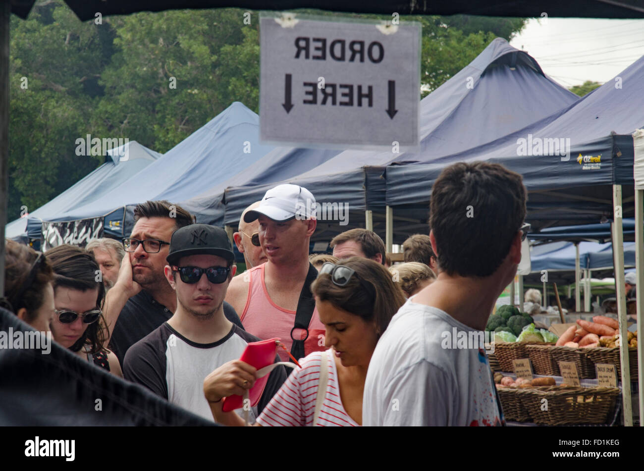 People in a que to place an order for food at a market stall - Stock Image
