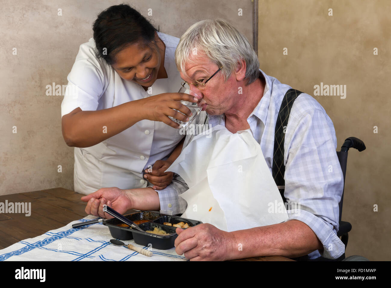Nurse in old people's home trying to make a patient eat his dinner - Stock Image