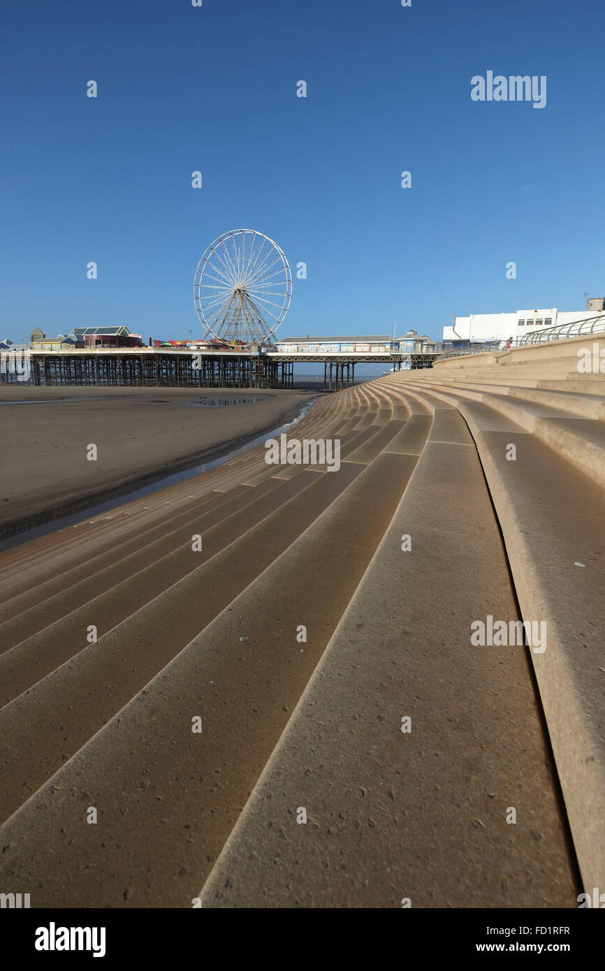 Steps down to the beach on Blackpool promenade with central pier in the background - Stock Image