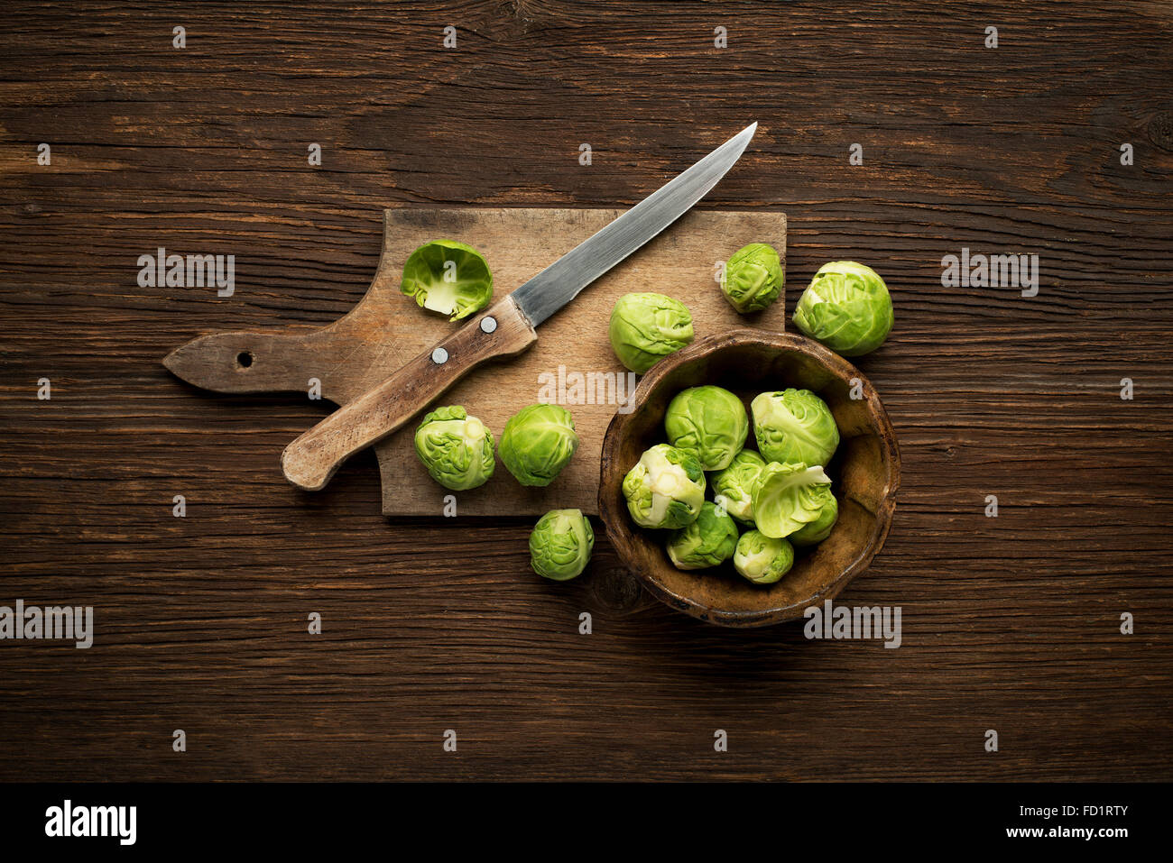 Fresh raw Brussels sprouts on a wooden background. - Stock Image
