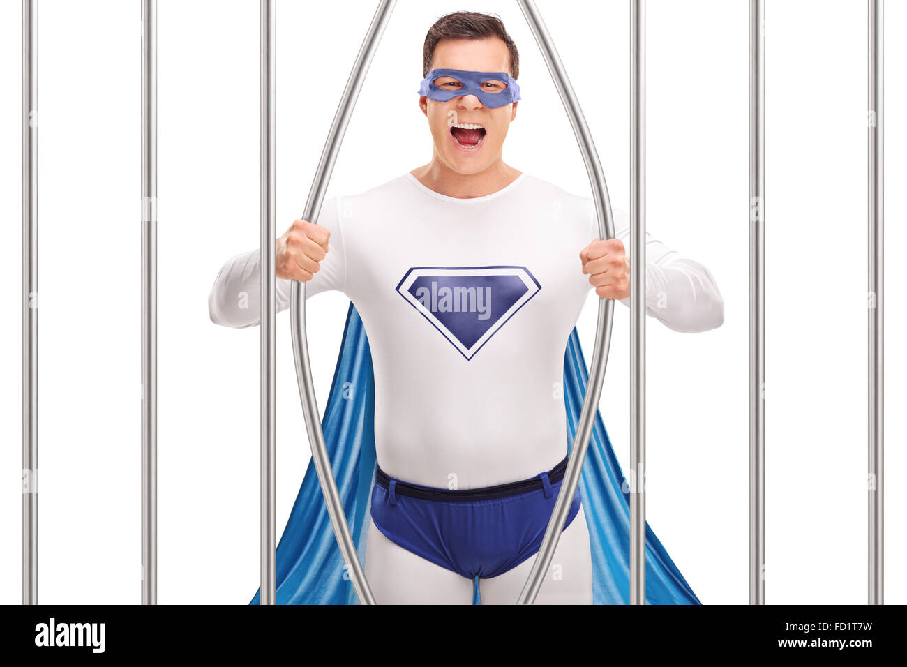 Young man in superhero costume breaking out of prison by bending the bars isolated on white background - Stock Image