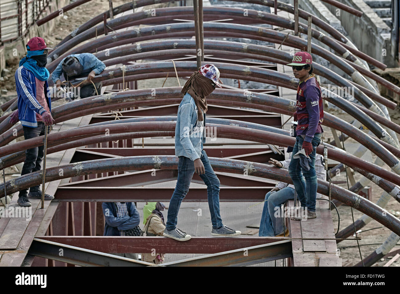 Thai construction site with barefoot workers, sneakers and baseball caps and oblivious to the health and safety - Stock Image