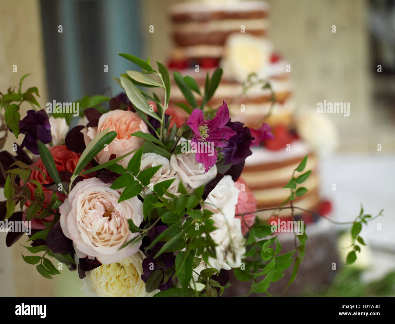 A luxurious wedding sponge cake with summer fruits and flowers - Stock Image
