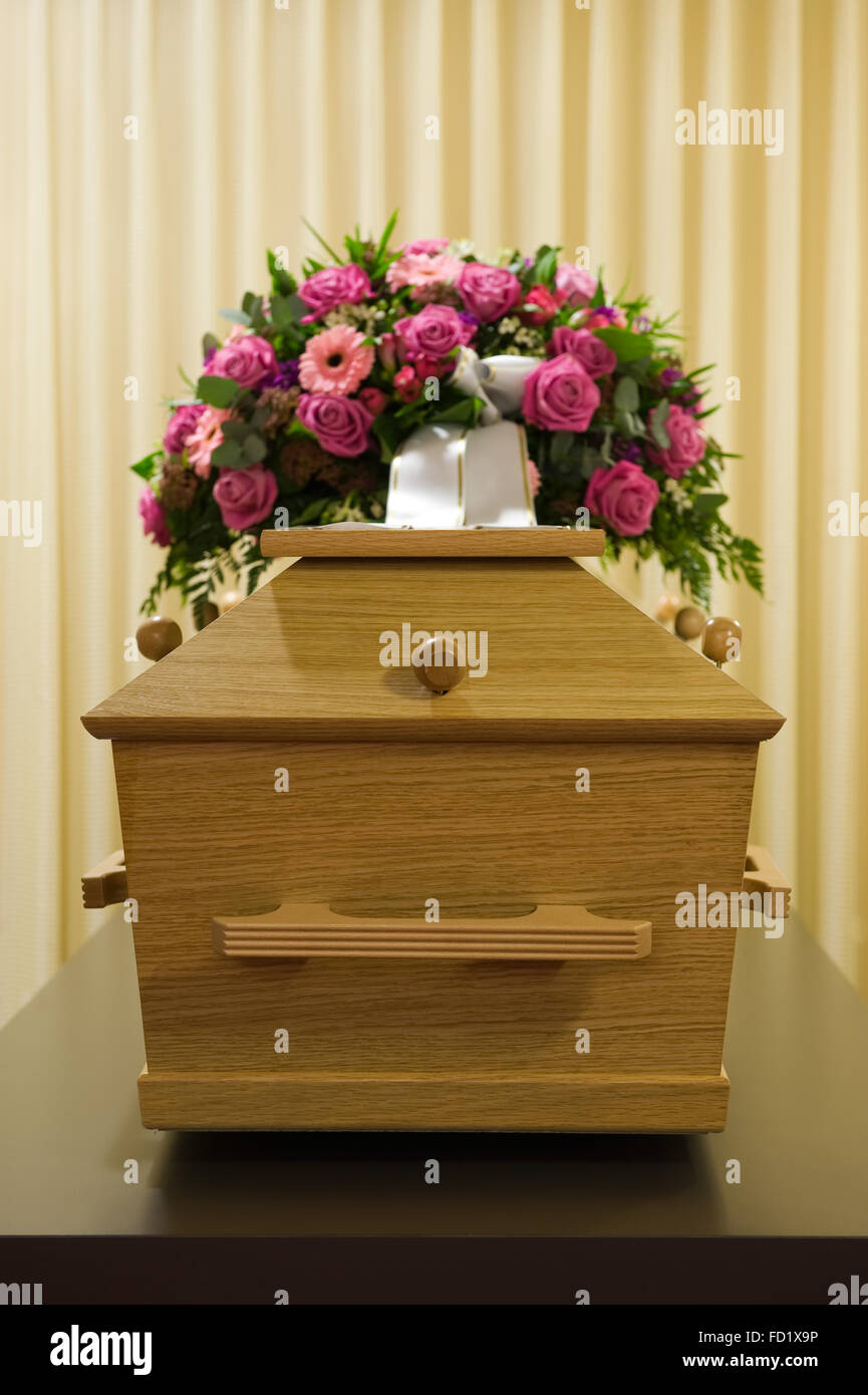 A coffin with a flower arrangement in a morgue - Stock Image