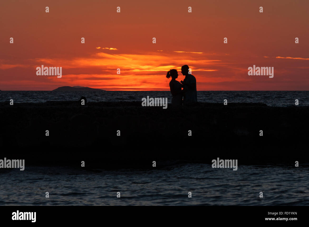 silhouette of couple facing each other with sunset backdrop - Stock Image