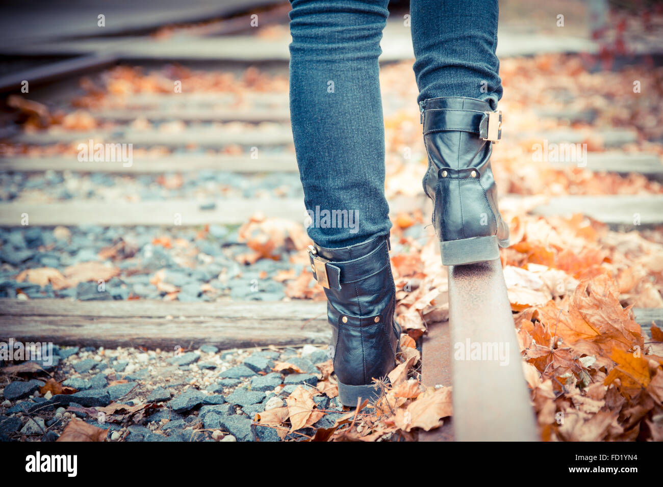 Black leather boots along old railroad tracks. Vintage toned image. - Stock Image