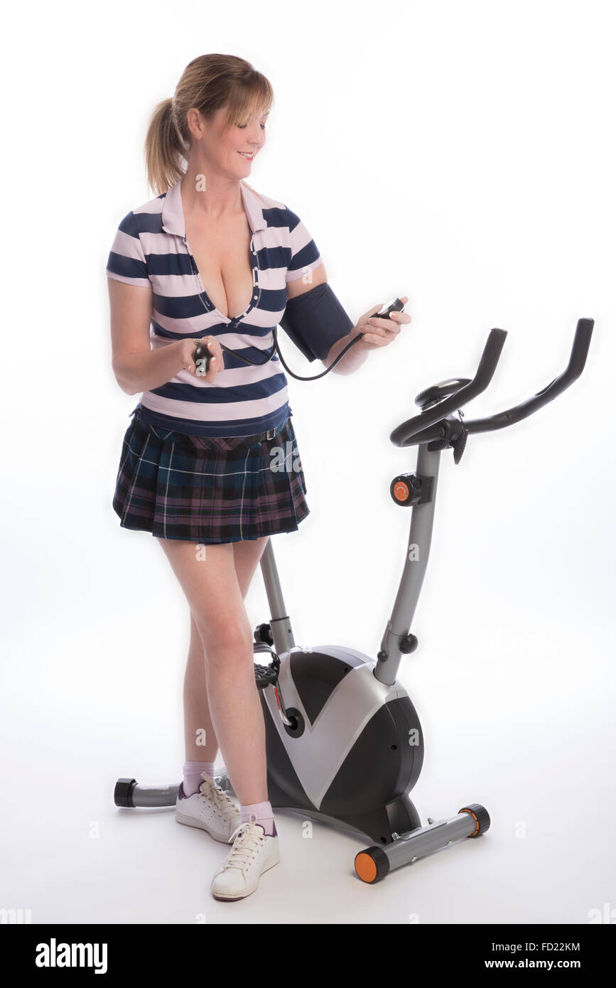 Woman checking blood pressure after using exercise bike - Stock Image