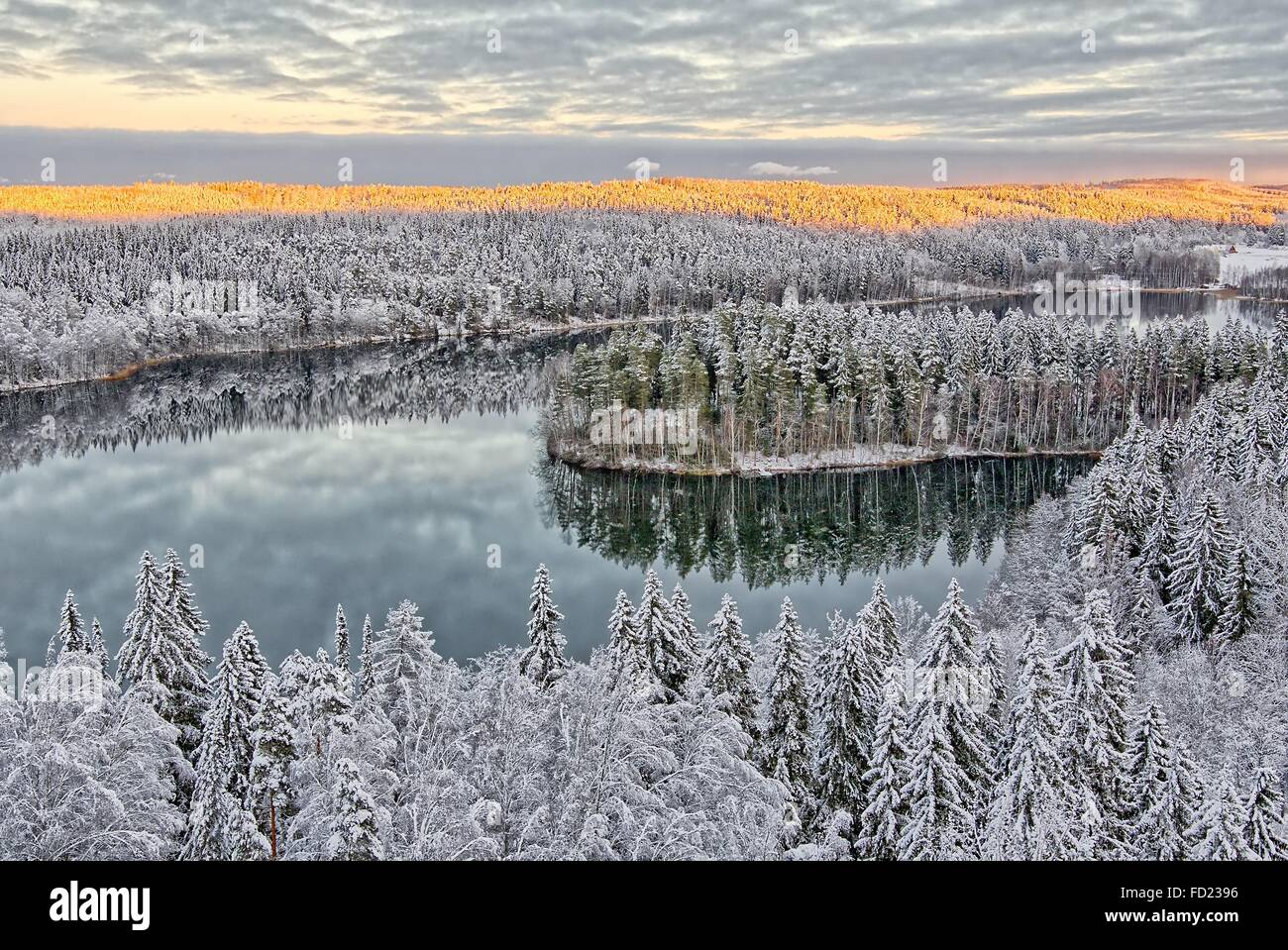 Aerial view of snowy lake and forest at Aulanko nature park in Finland. Late afternoon Sun shining in frozen landscape. Stock Photo