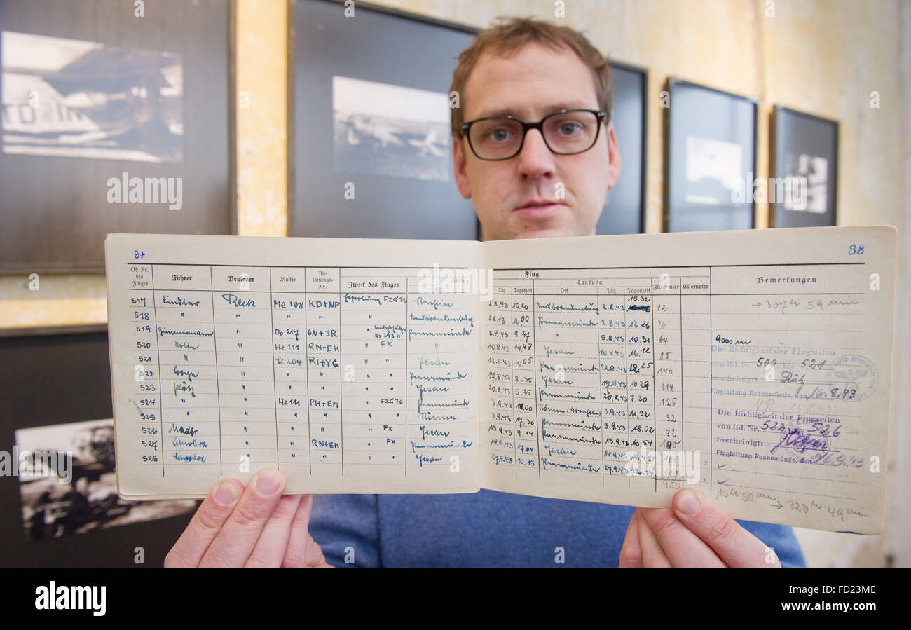 Philipp Aumann, exhibition curator at the Peenemuende Historical Technical Museum, holds up a log book of the flyer Stock Photo