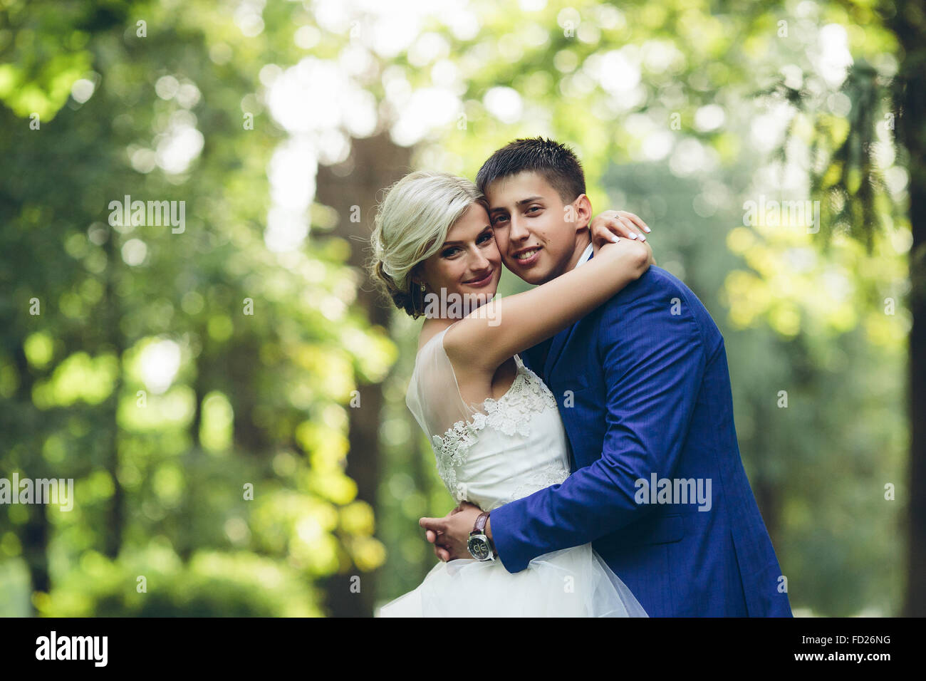 Beautiful wedding couple hugging in the park - Stock Image