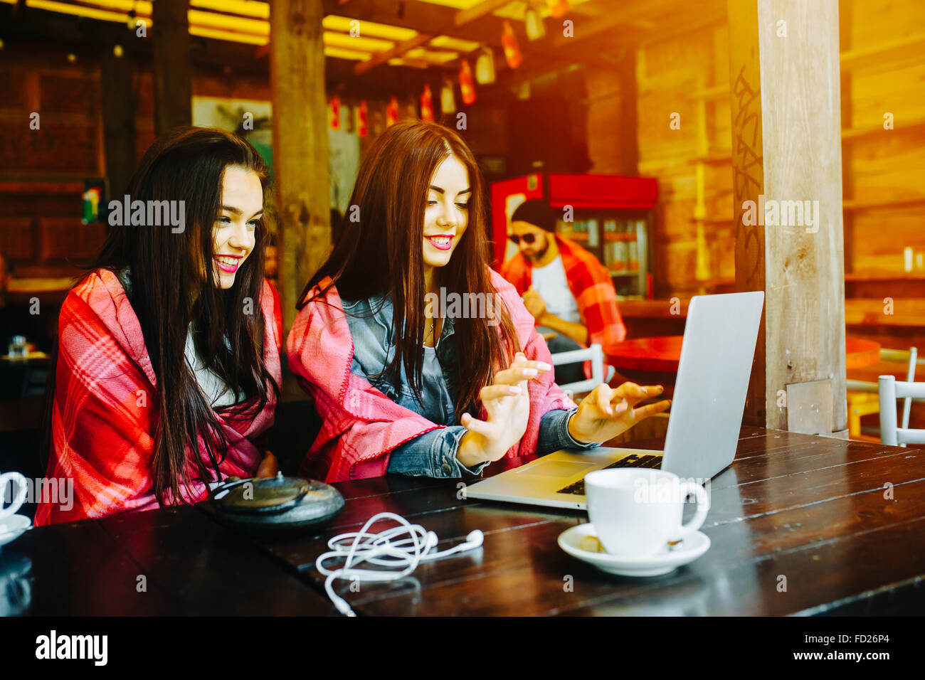two girls watching something in laptop - Stock Image