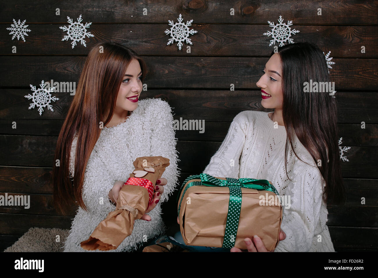 Two beautiful girls offer gifts to camera - Stock Image