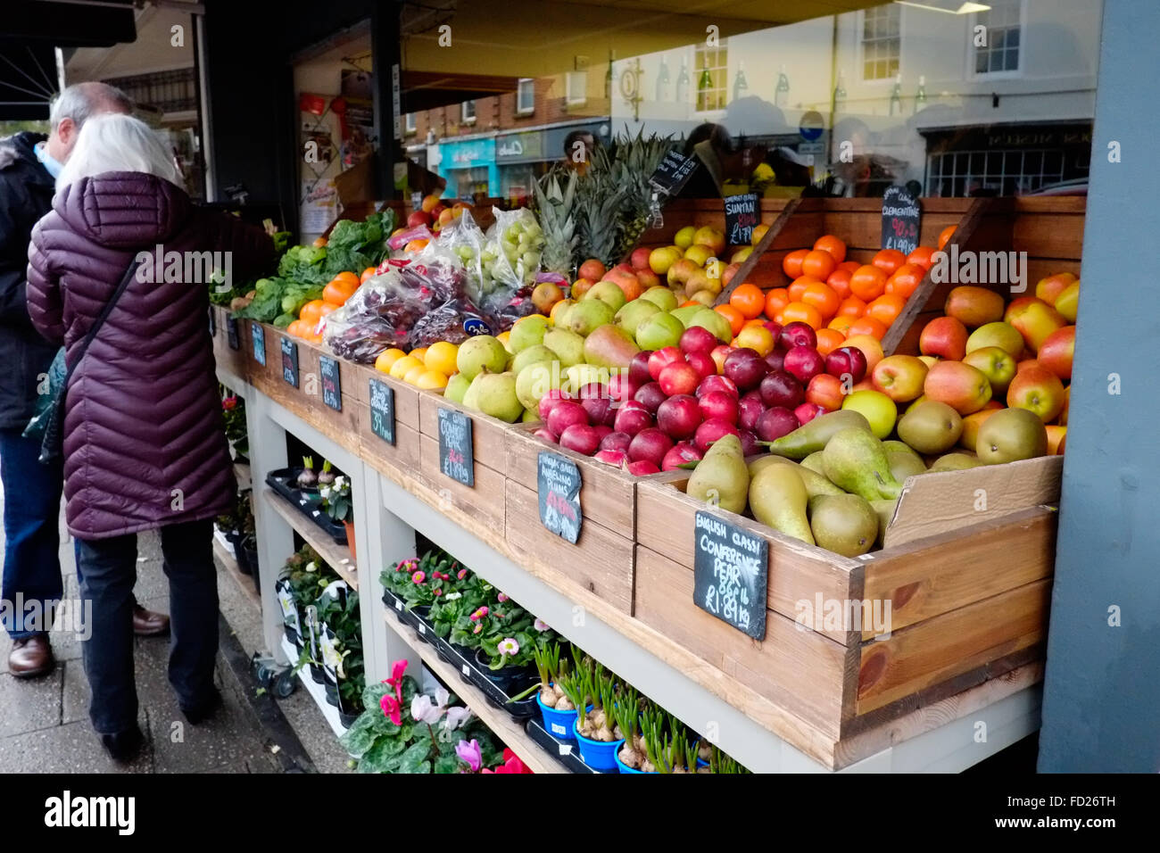 A display of fresh fruit for sale outside of a greengrocers shop on a high st in an english town Stock Photo