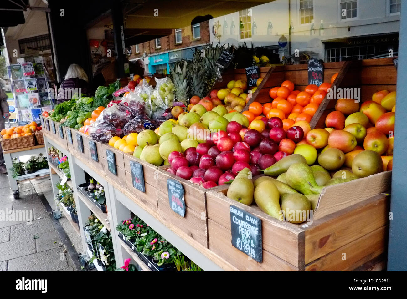 A display of fresh fruit for sale outside of a greengrocers shop on a high st in an english town - Stock Image