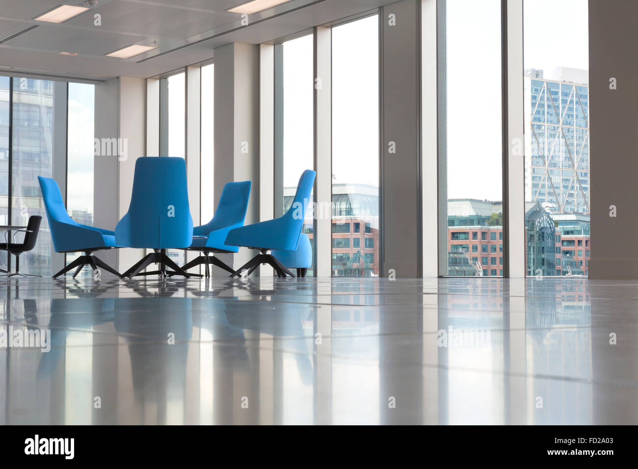 Modern office interior with glass windows and comfortable blue arm chairs in the corner - Stock Image