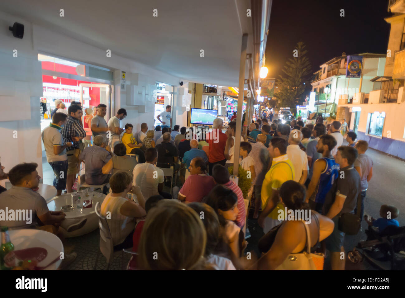 Spectators on the terrace of a bar and street watching the television broadcast of a soccer game in southern Italy - Stock Image