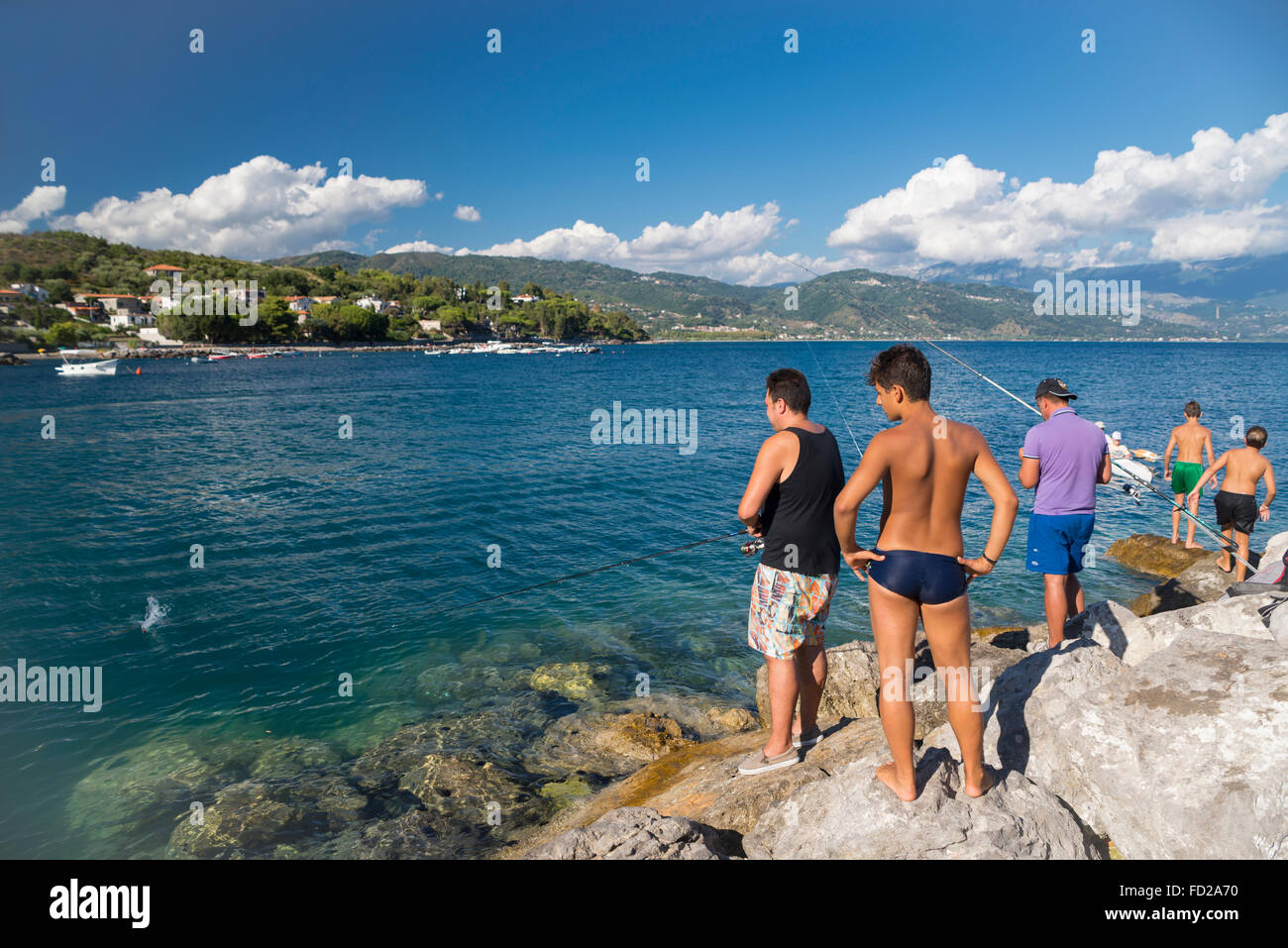 Anglers in the port of Scario in the Gulf of Policastro on a sunny summer day, Cilento, Italy - Stock Image