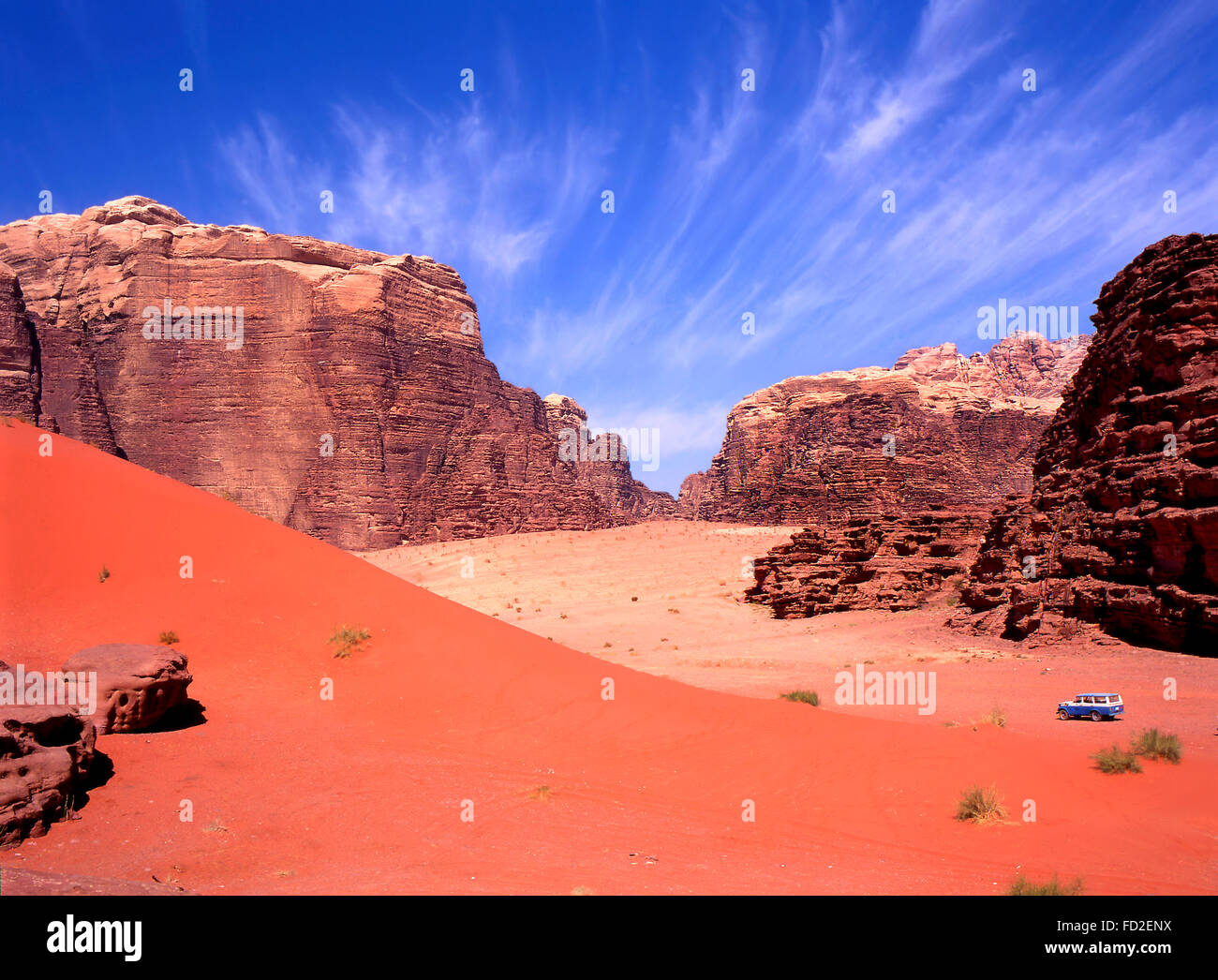 Four wheel drive in Wadi Rum, Jordan. Blue sky fades to red sand with tourists in 4wd on a tour in this desert. - Stock Image