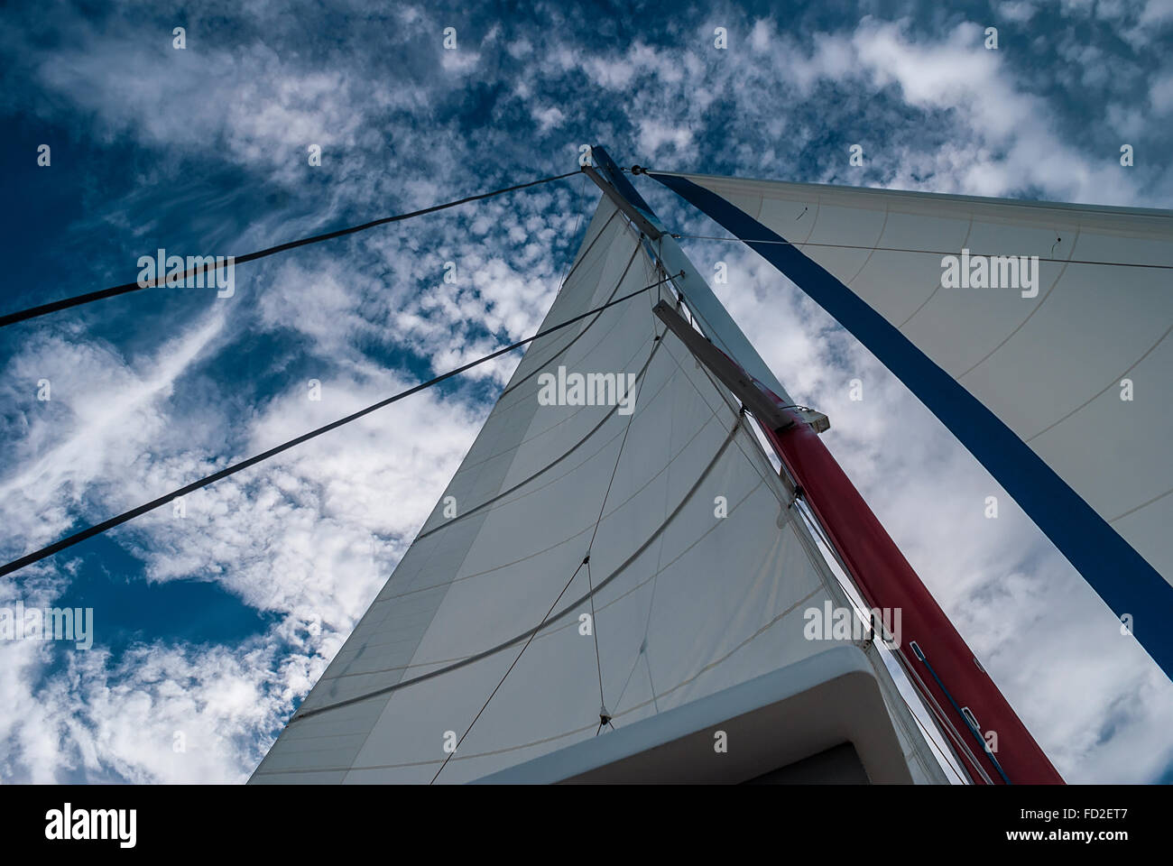 The mast and sails recreational catamaran on a background of cloudy sky - Stock Image