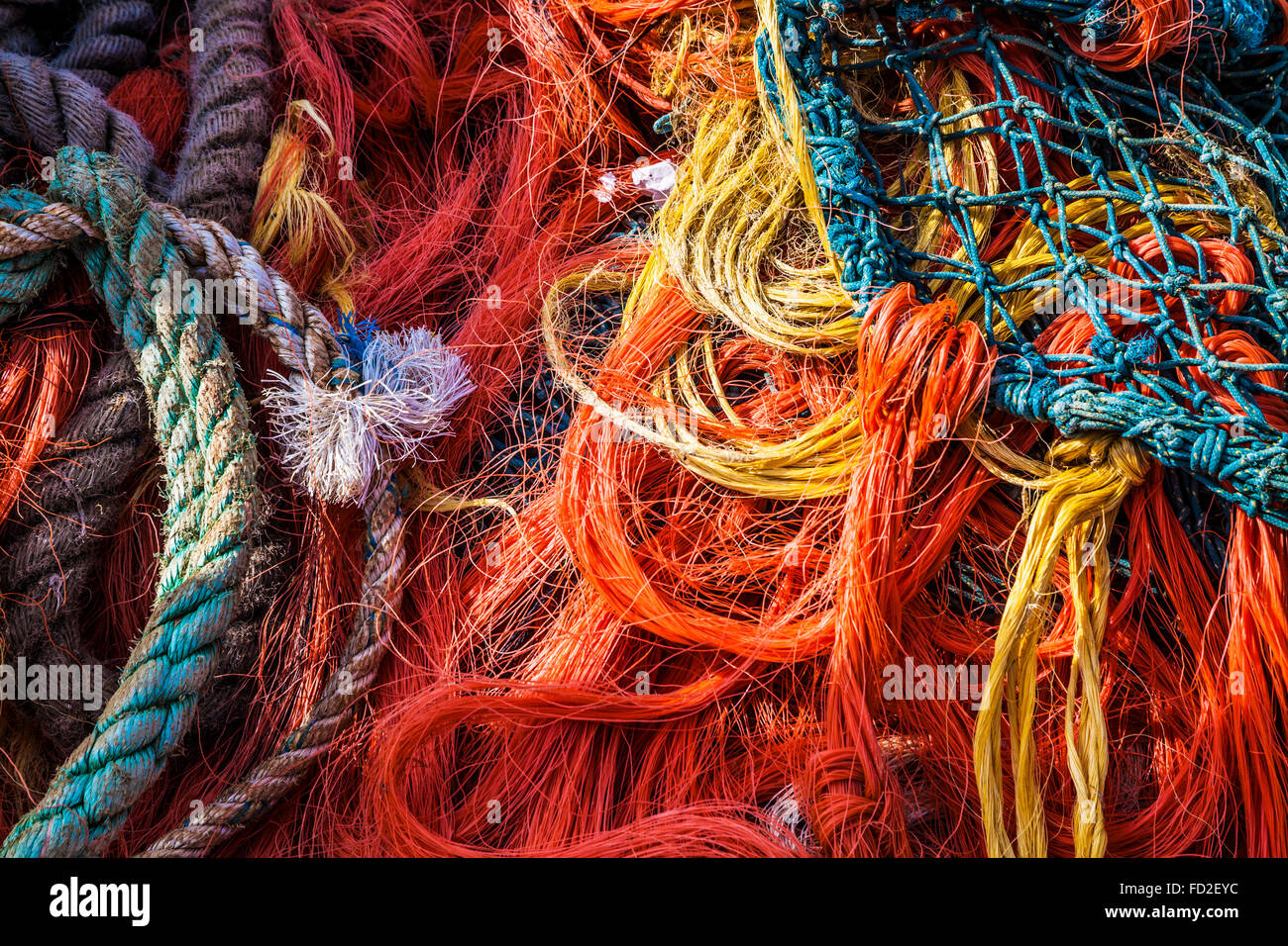 An abstract image of blue and orange fishing nets and ropes. - Stock Image
