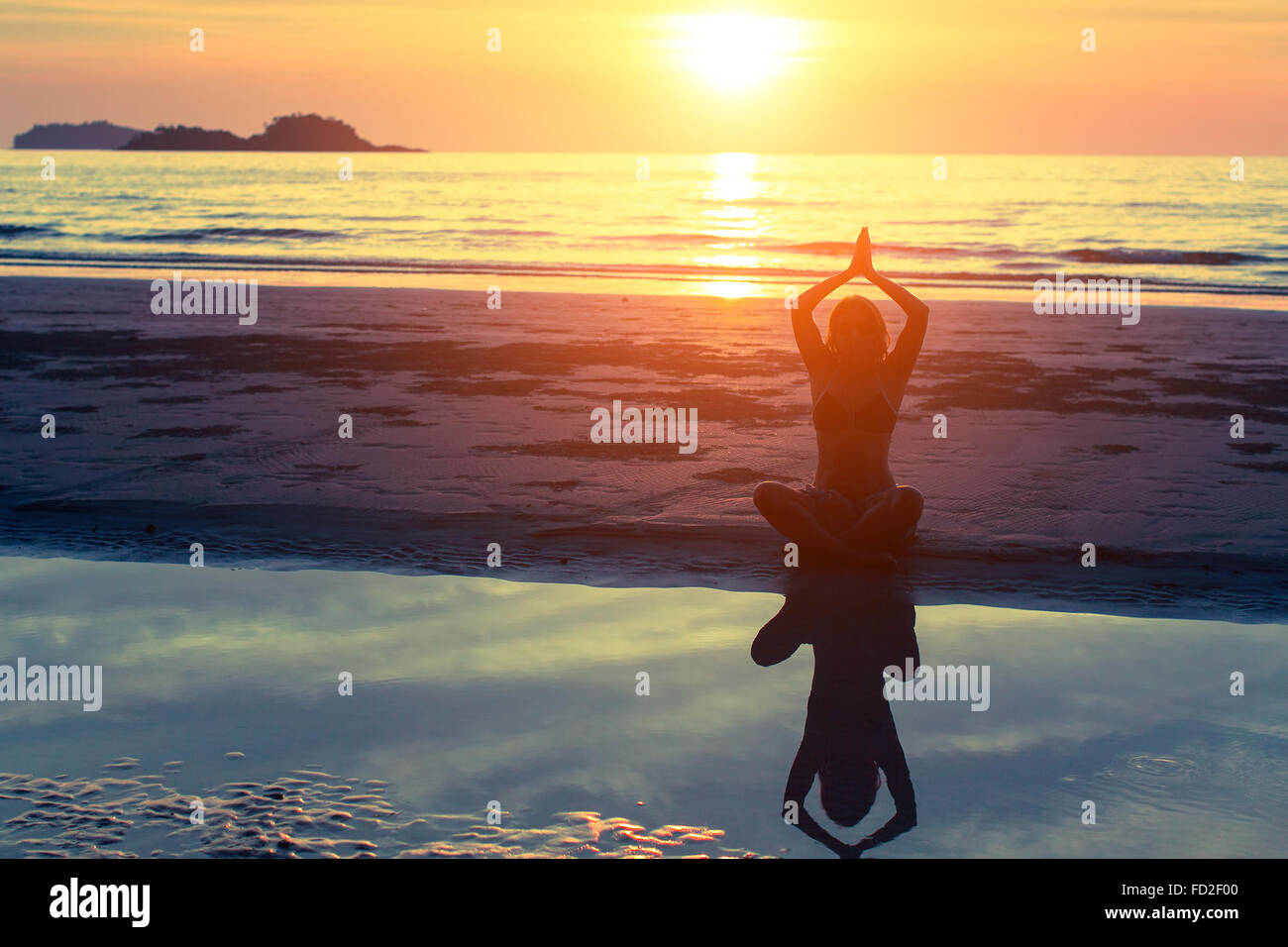 Woman silhouette practicing yoga on the beach at amazing sunset. - Stock Image