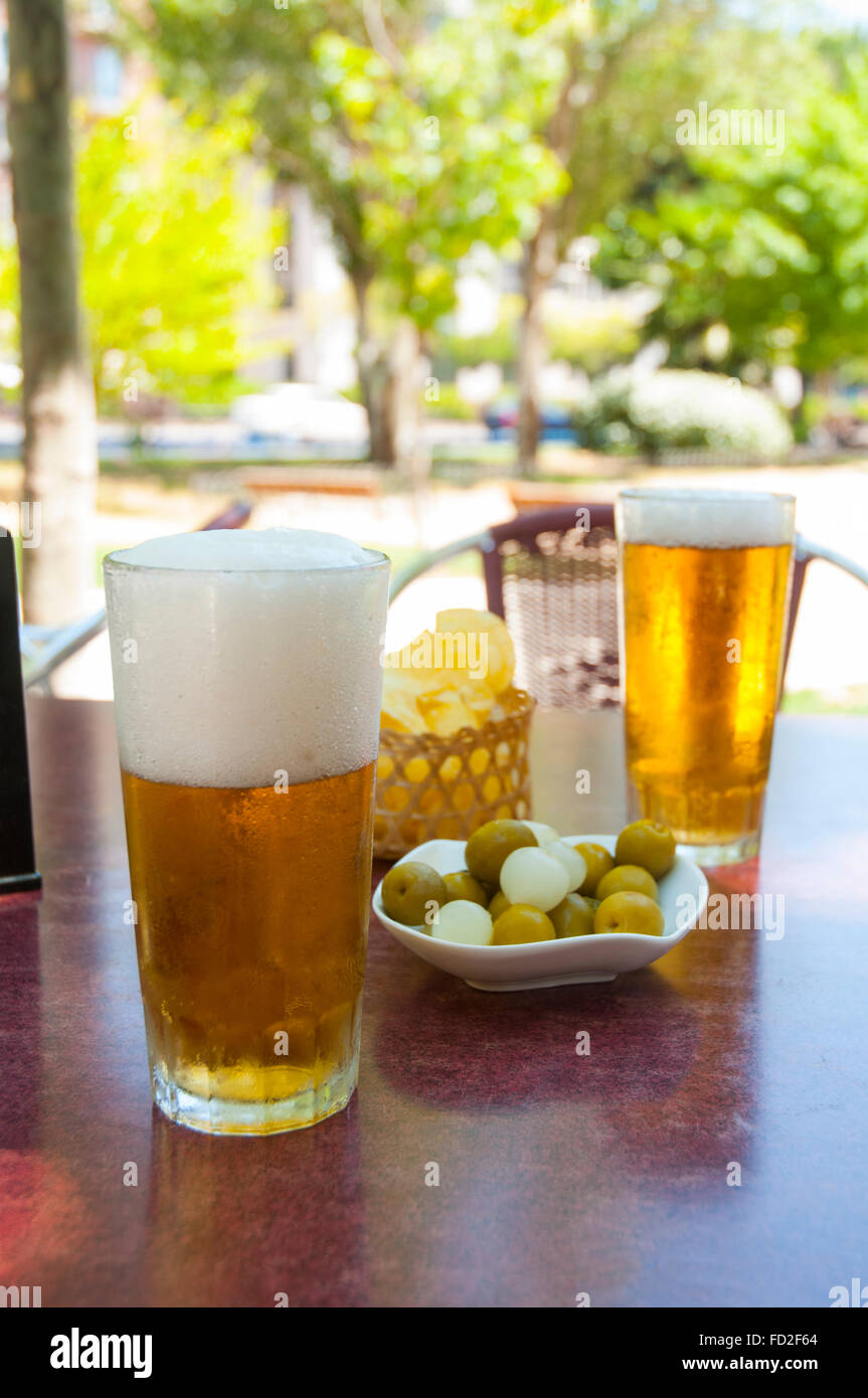 Two Glasses Of Beer And Green Olives In A Summer Terrace