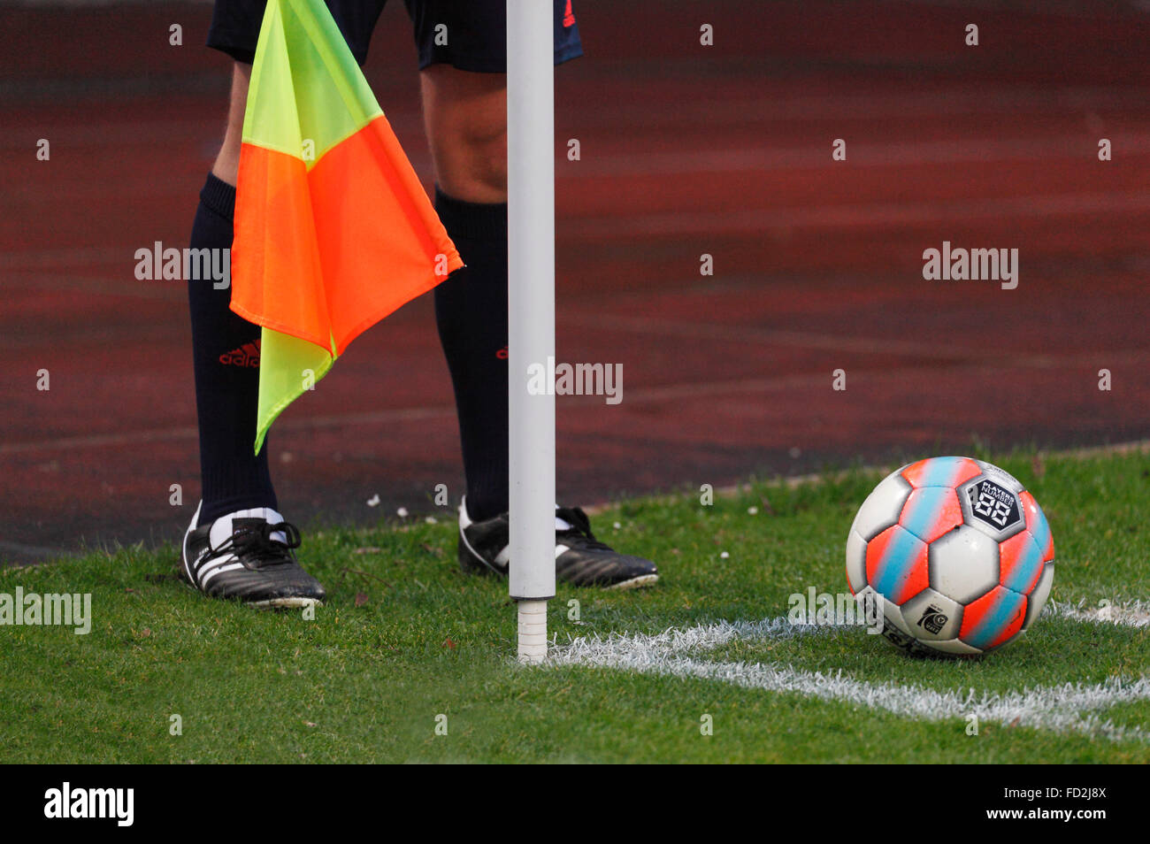 sports, football, symbolism, ball lies at the corner flag for a corner kick, linesman with flag, assistant referee - Stock Image