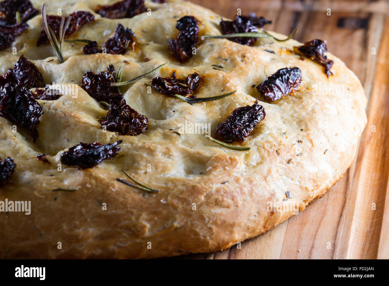 close up of a home made focaccia roll with sun dried tomatoes and fresh rosemary sprigs on top - Stock Image