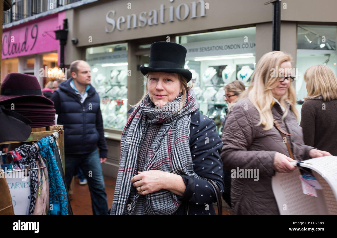 Woman wearing a black top hat bought at Kensington Gardens hat stall and shop in North Laine area of Brighton UK - Stock Image