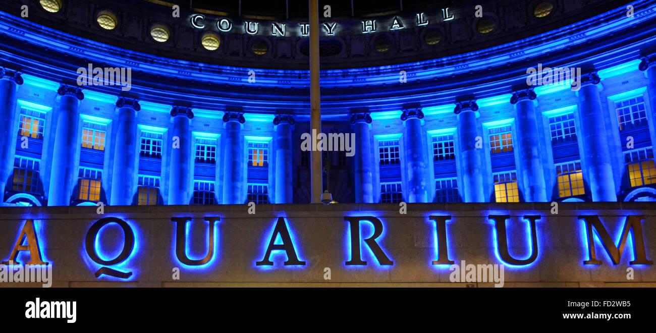 Illuminated sign for the London Aquarium with floodlighting on the old County Hall building on the Thames embankment - Stock Image