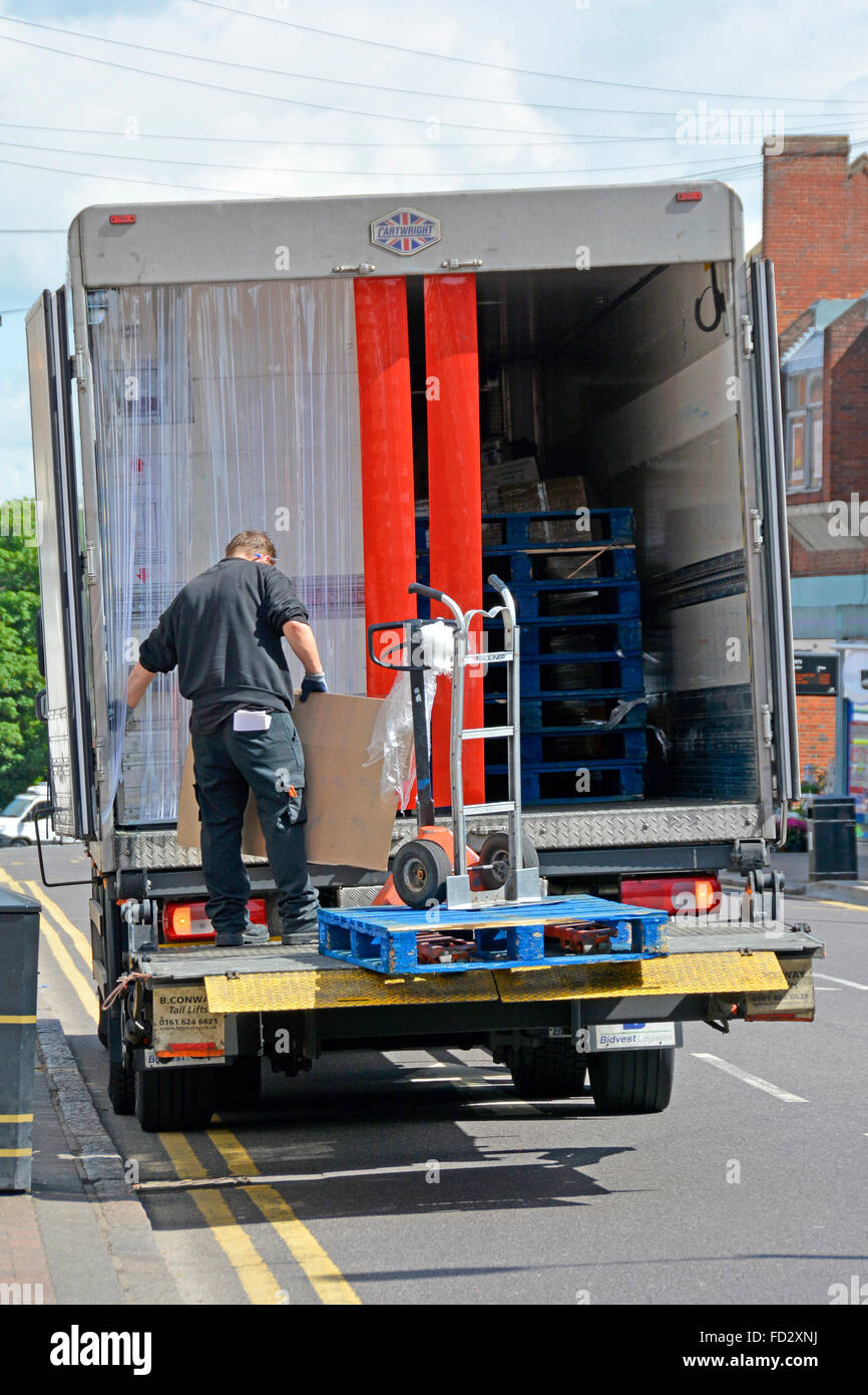 Lorry driver sorting pallet delivery standing on tailgate platform hoist outside high street shop England UK - Stock Image
