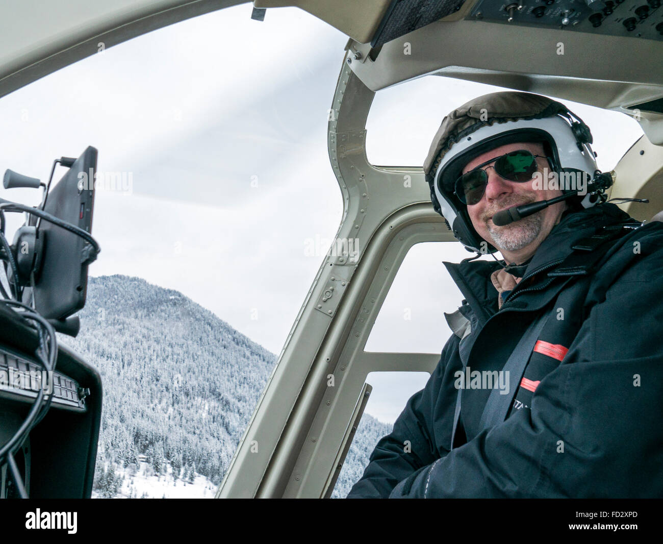 Helicopter pilot flying back country skiers into Selkirk Mountains near remote Mount Carlyle Lodge;  British Columbia; - Stock Image