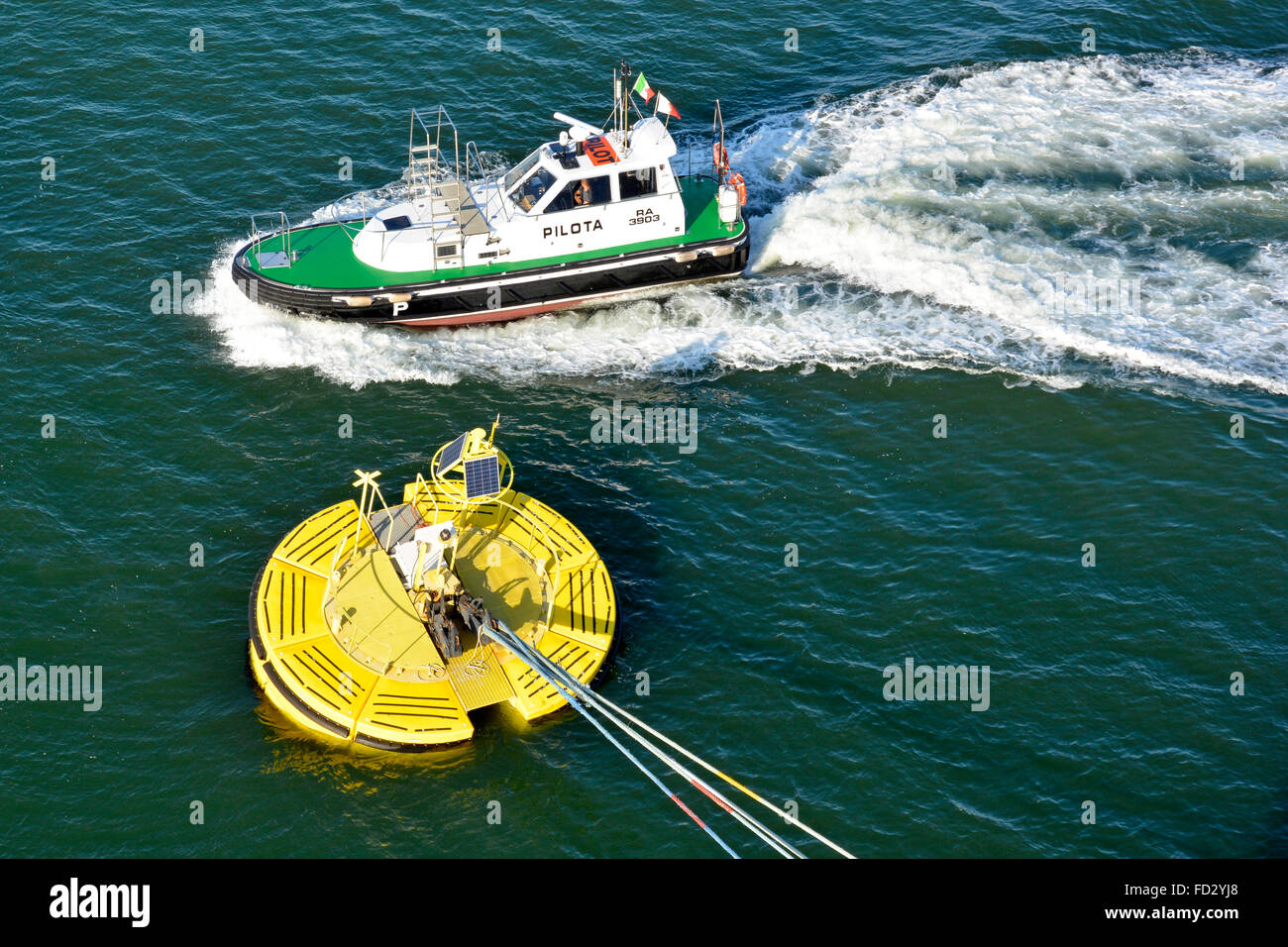 Pilots boat passing cruise ships mooring hawsers hooked onto floating buoy anchored to sea bed Stock Photo