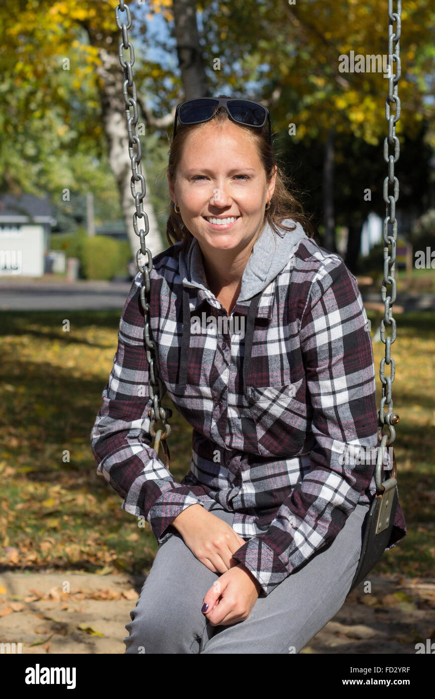 smiling women on a swing at fall - Stock Image