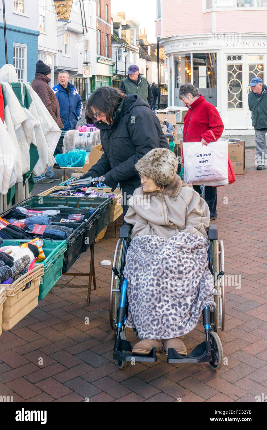 A 95 year old lady shopping on Faversham market with her carer or assistant.  MODEL RELEASED. Stock Photo