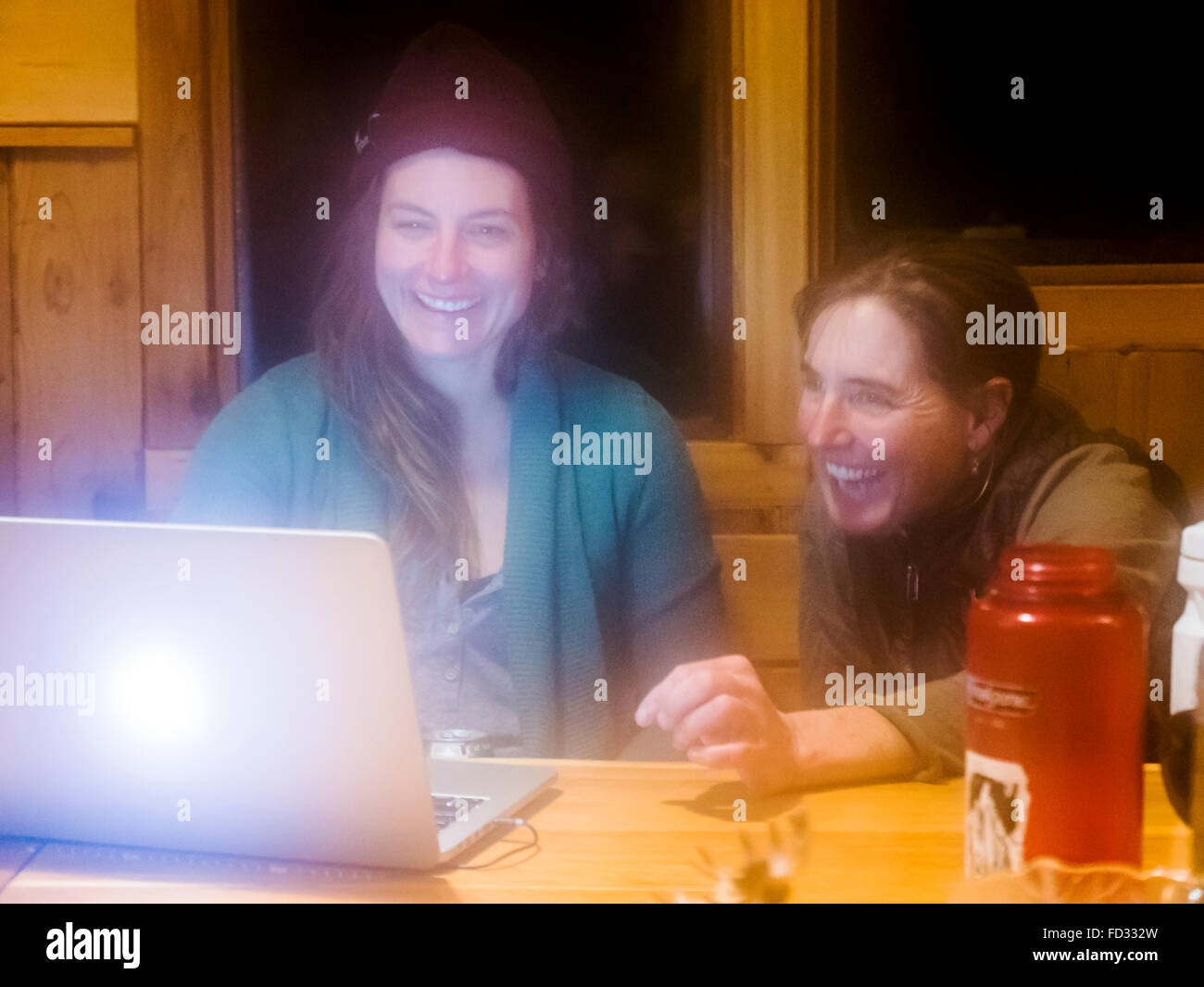 Two female back country skiers view photos on computer laptop; inside remote Mount Carlyle Lodge; British Colombia, - Stock Image