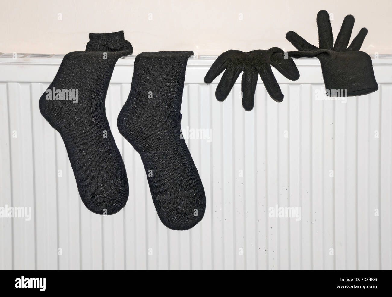 a black pair of wet  gloves and socks dry on a radiator in a room. - Stock Image