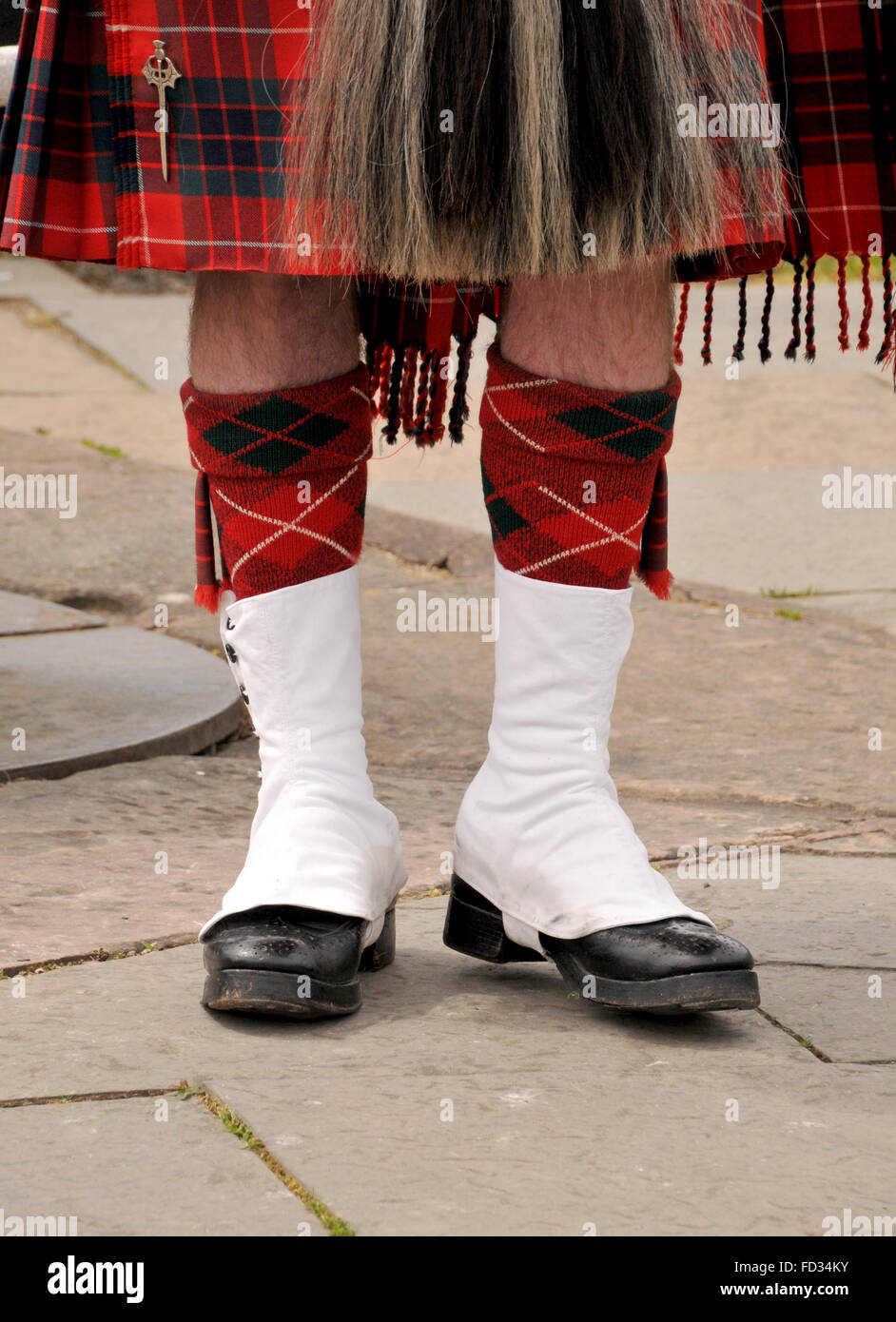 legs and footwear of a standing Scottish man dressed in a red checked tartan kilt. - Stock Image
