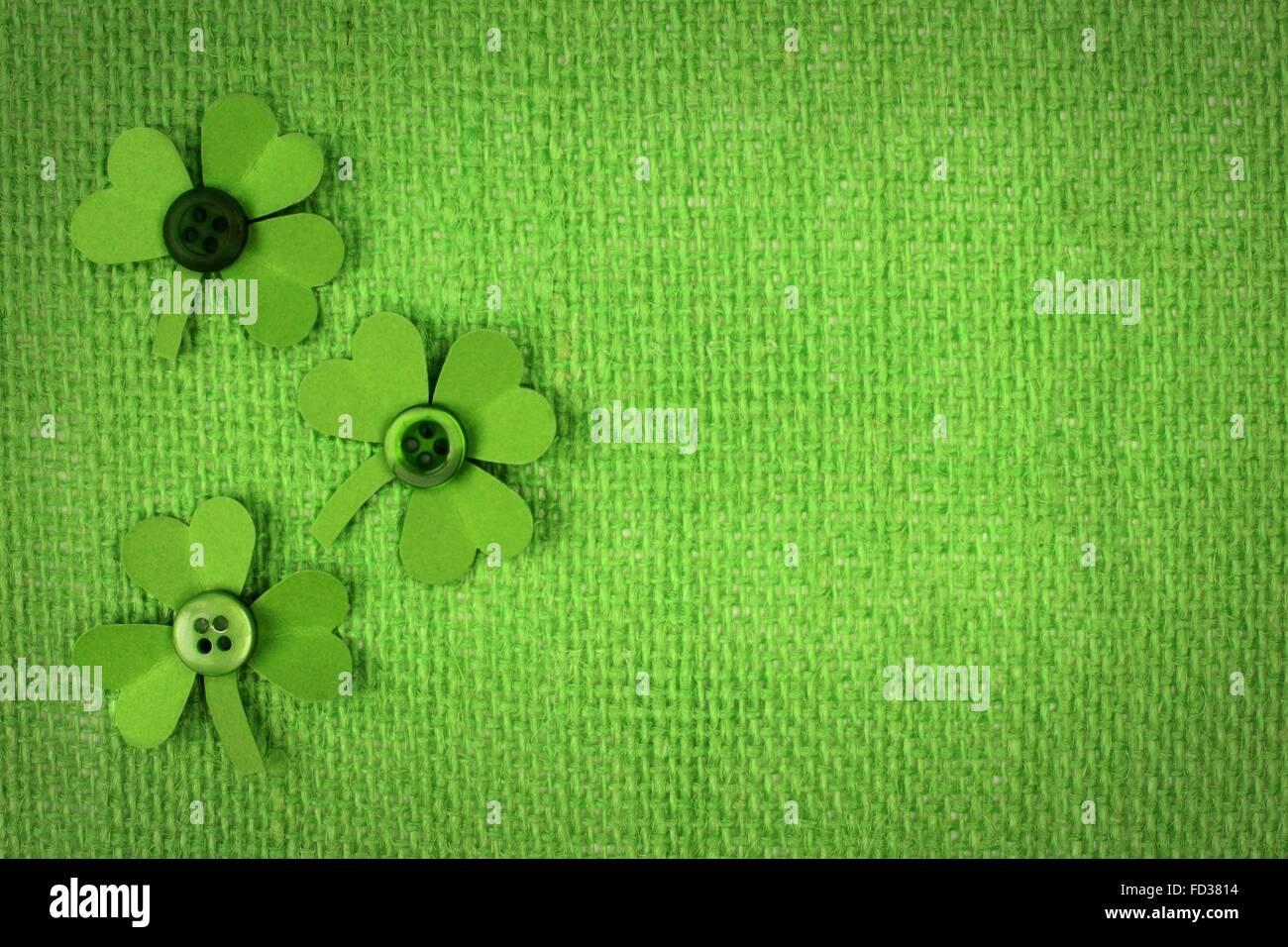 St Patricks Day green burlap with paper handmade shamrocks - Stock Image