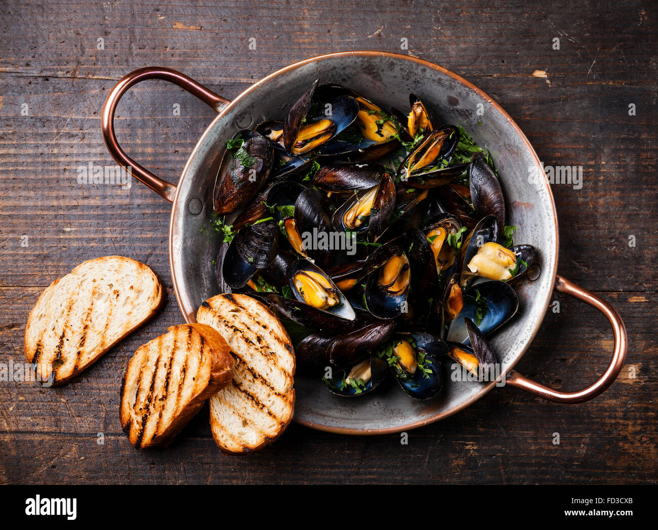 Mussels in copper cooking dish and bread toasts on dark wooden background Stock Photo