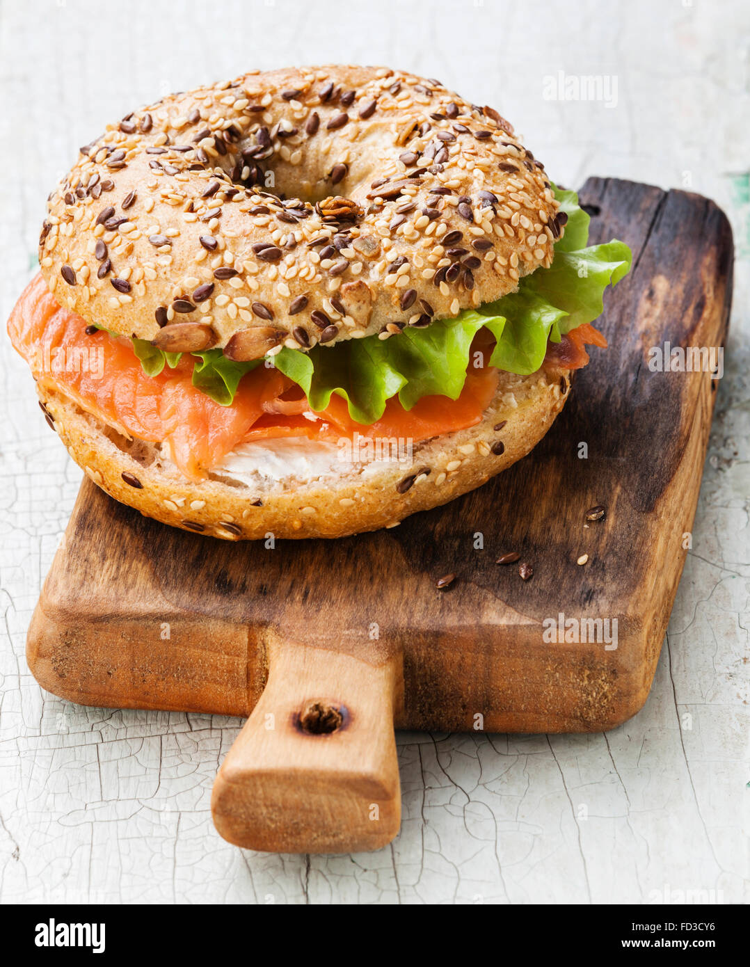 Salmon Bagel Sandwich with cream cheese and grain on blue wooden background - Stock Image