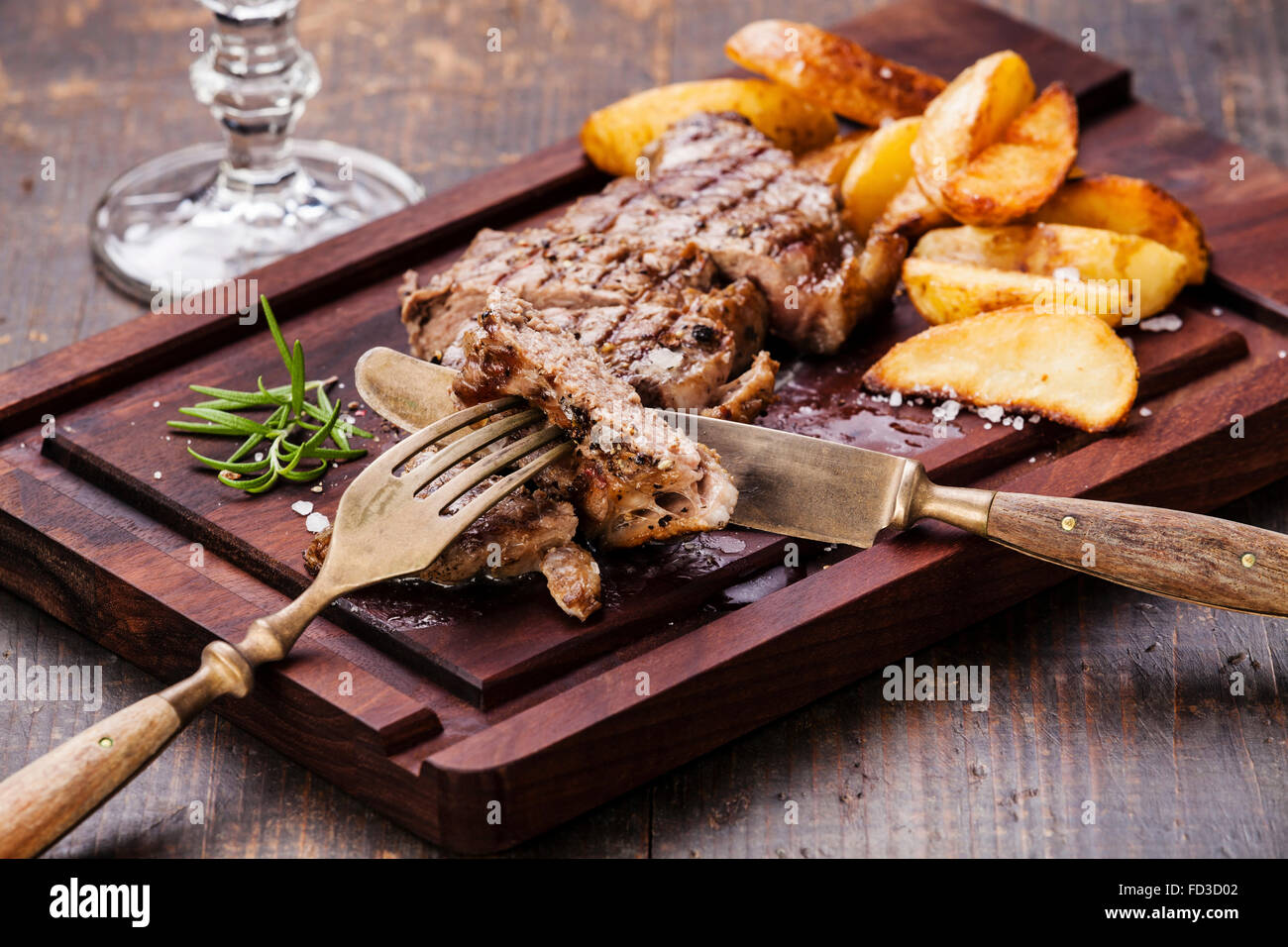 Sliced well done grilled New York steak with roasted potato wedges on cutting board on wooden background - Stock Image