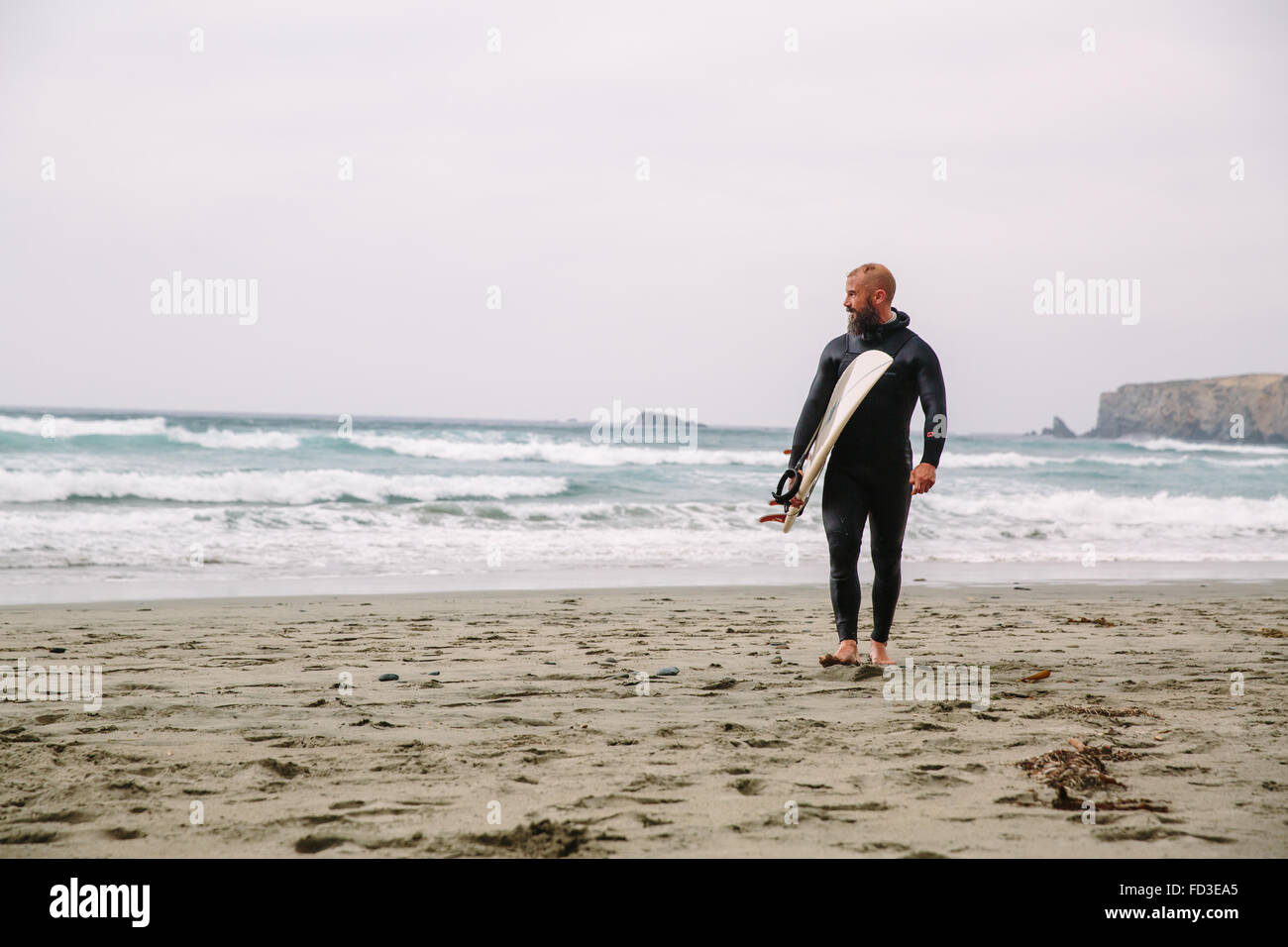 A surfer walks in from the water after a day out on the waves in Big Sur, California. Stock Photo