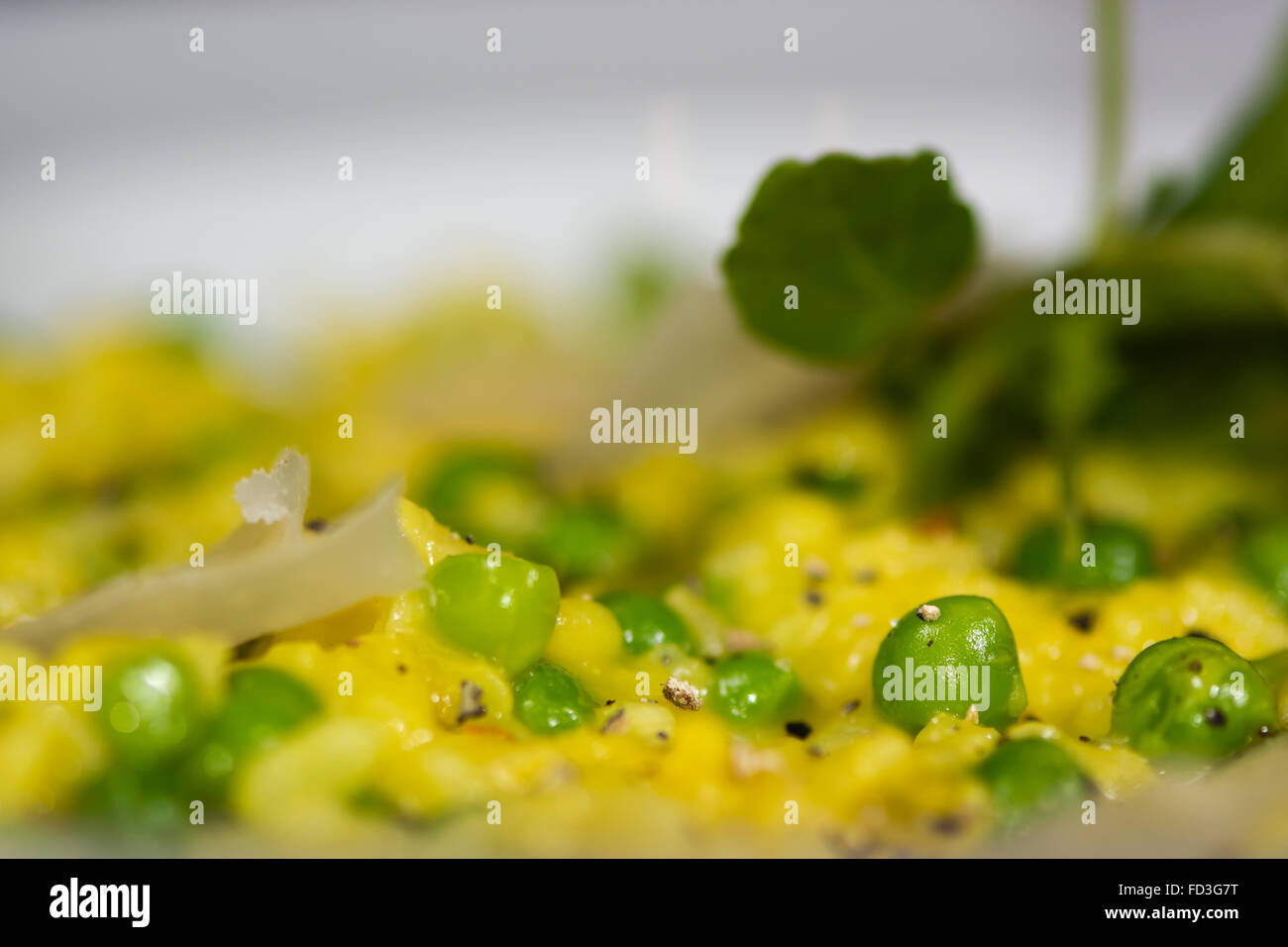 Leek, garden pea and saffron risotto close up. French restaurant prepared cuisine with bright yellow rice - Stock Image