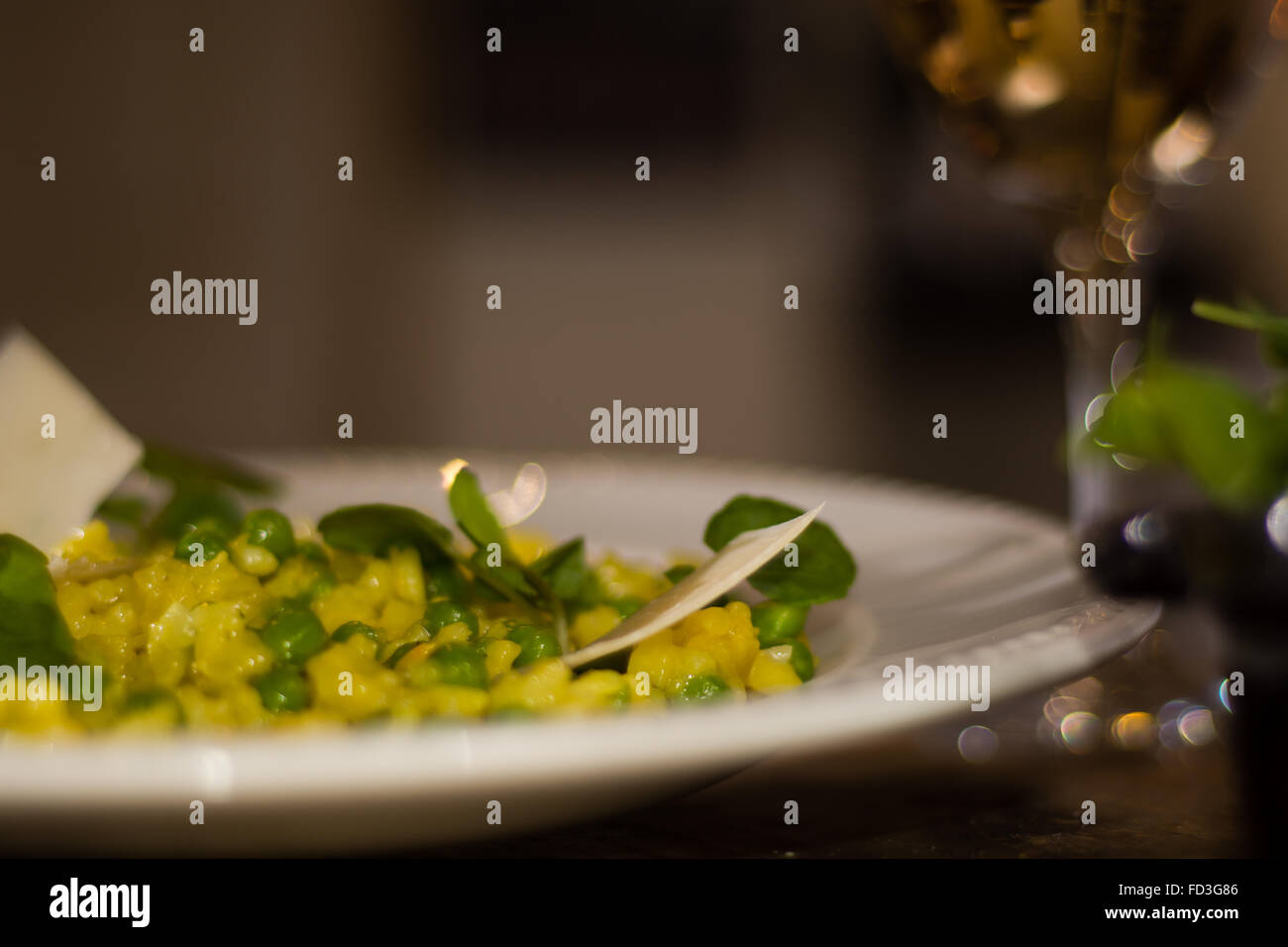 Leek, garden pea and saffron risotto half plate with wine. French restaurant prepared cuisine with bright yellow - Stock Image