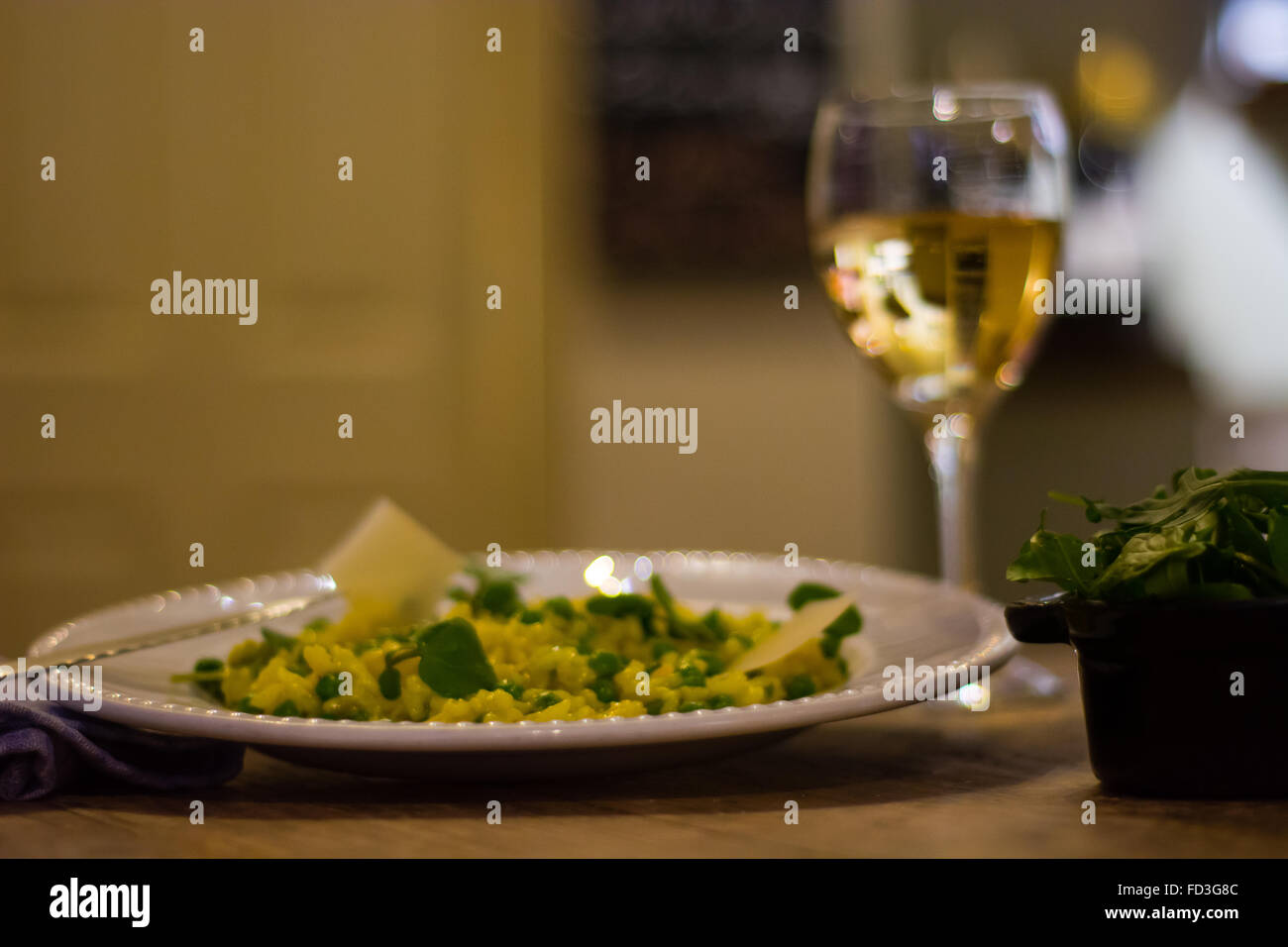 Leek, garden pea and saffron risotto plate with wine. French restaurant prepared cuisine with bright yellow rice - Stock Image