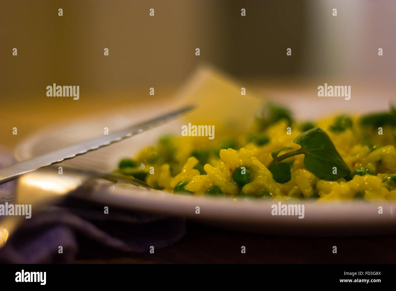 Leek, garden pea and saffron risotto half plate with knife. French restaurant prepared cuisine with bright yellow - Stock Image