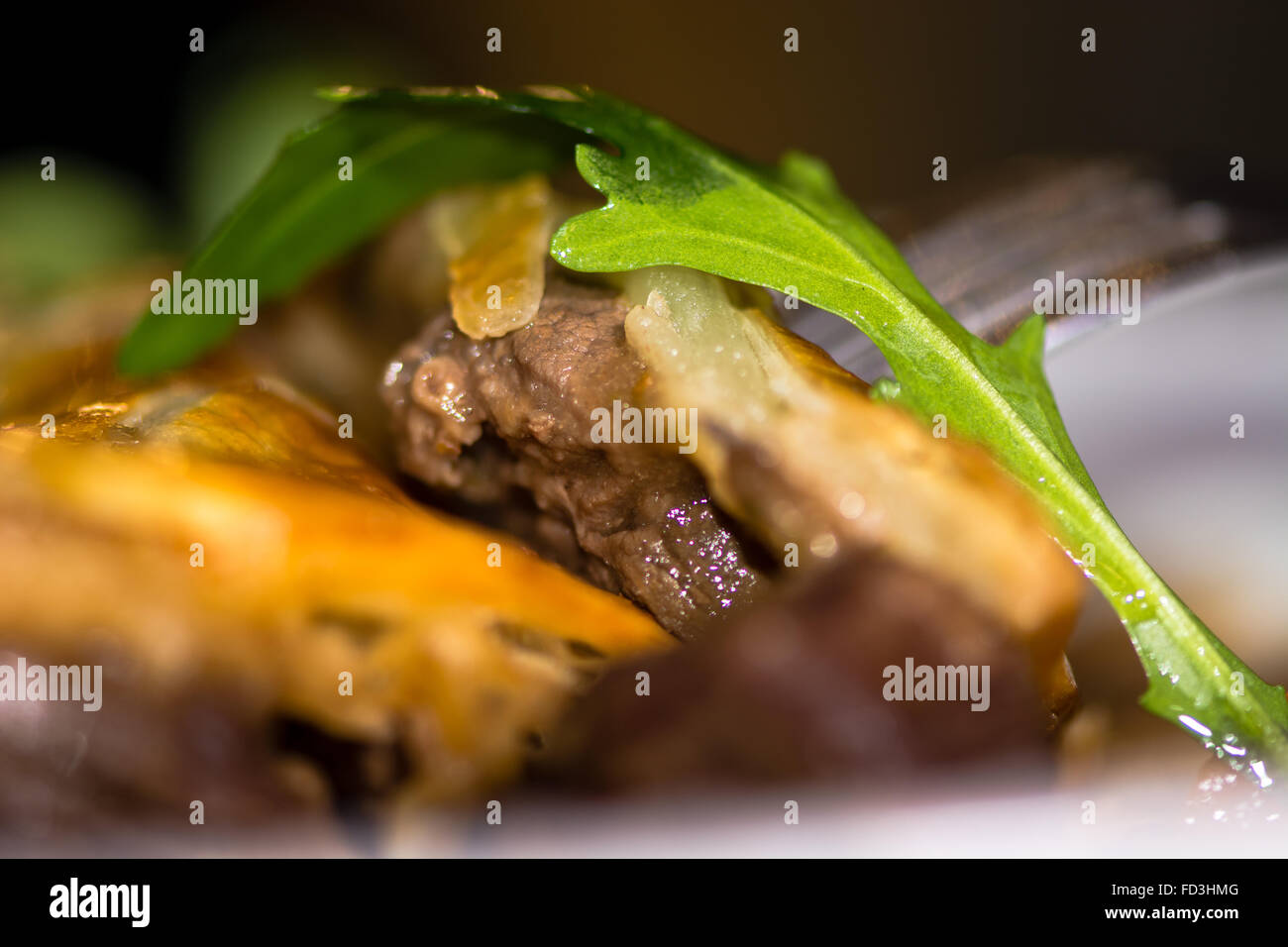 Steak and kidney pie close up of meat with rocket leaf. French restaurant cuisine influenced by traditional English - Stock Image