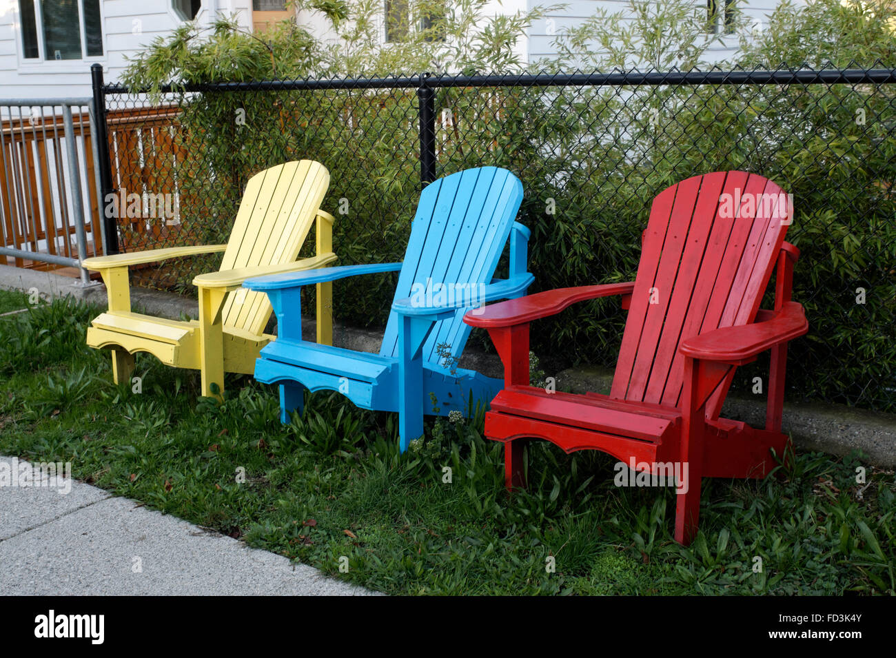 Three Wooden Adirondack Chairs Painted In The Primary Colors Red, Yellow,  And Red